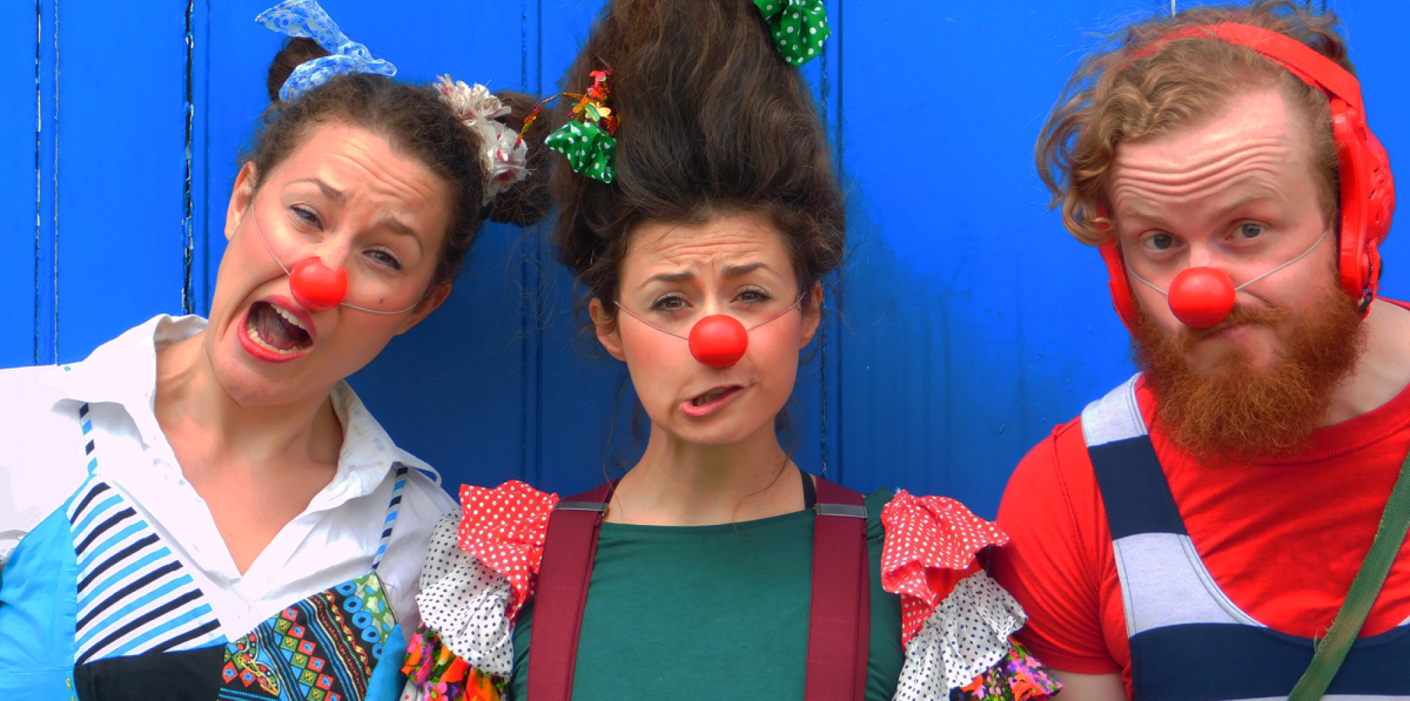 Better Together: three clowns with red noses and red cheeks standing in front of a blue door, pulling funny faces