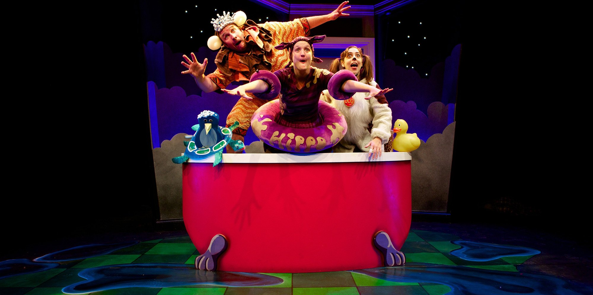3 performers dressed as different animals and make believe creatures sit in a big red bath with a rubber duck and a penguin