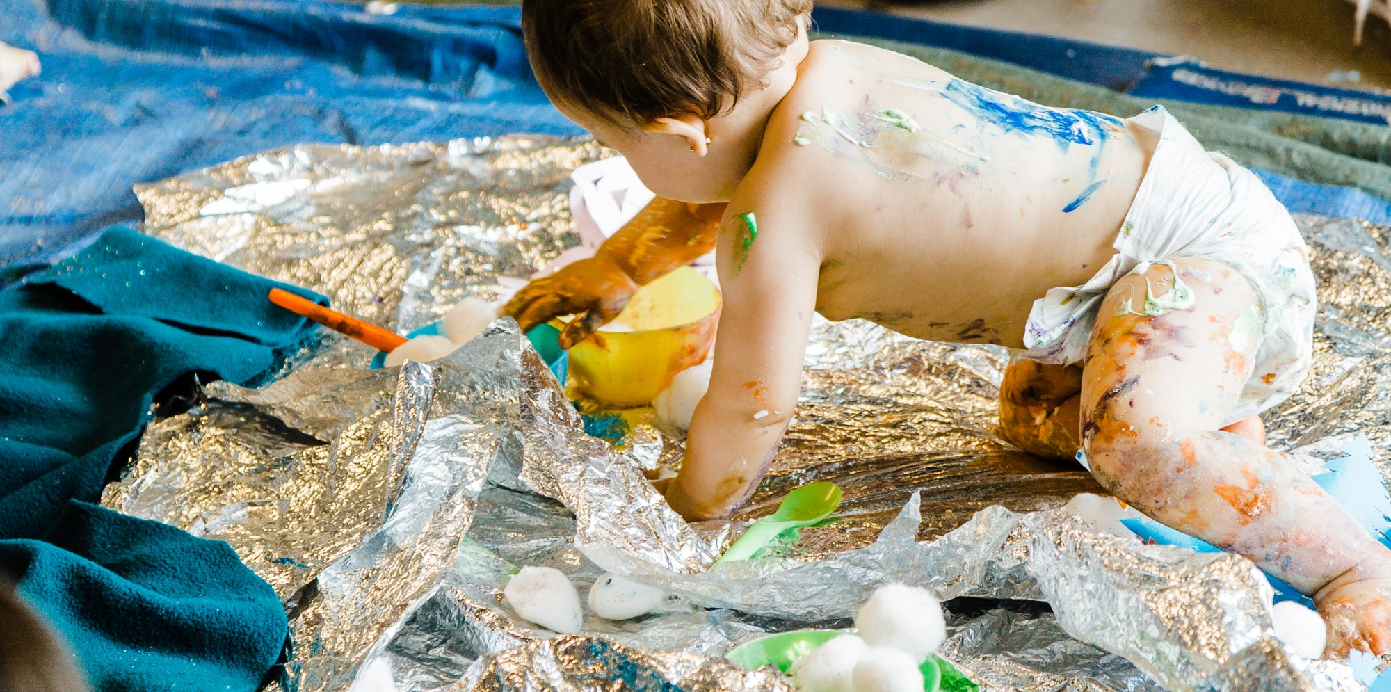 a baby on tin foil covered in paint
