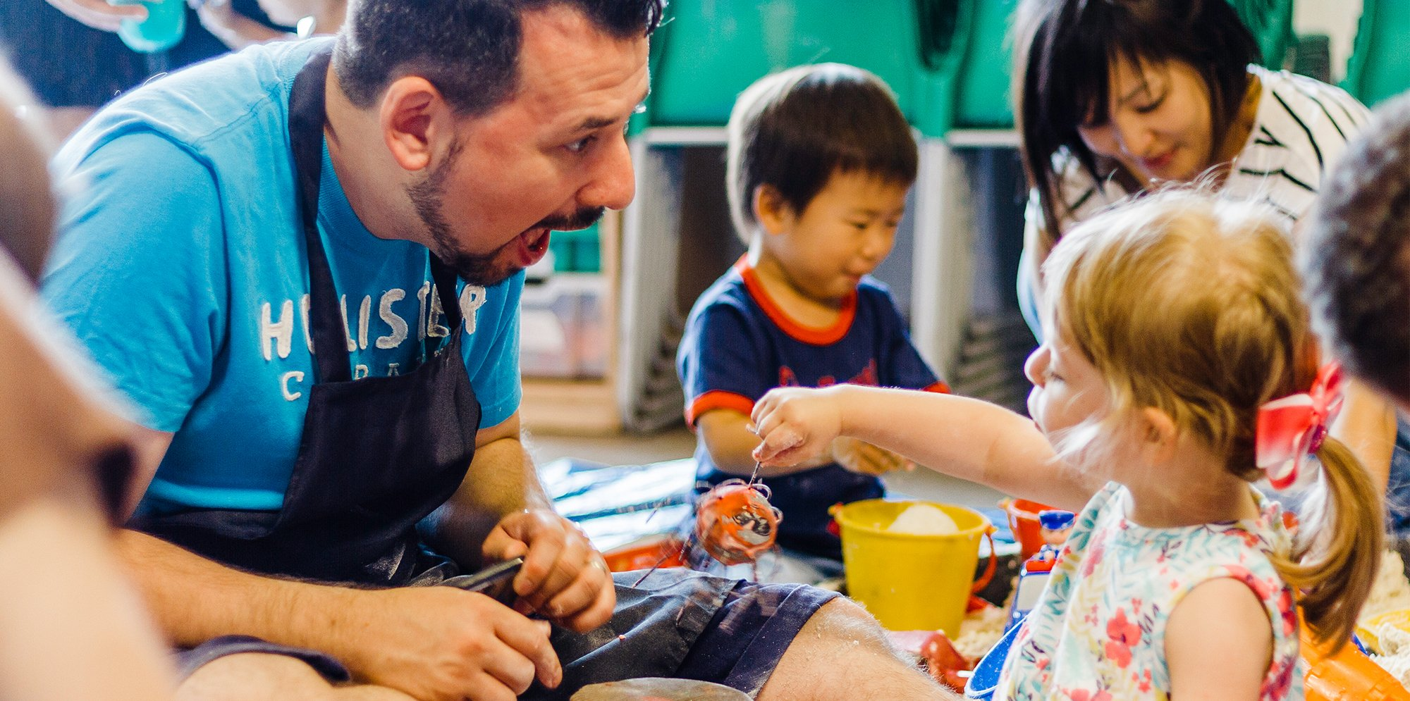 A toddler plays with some crafts while an adult pulls a funny face at them