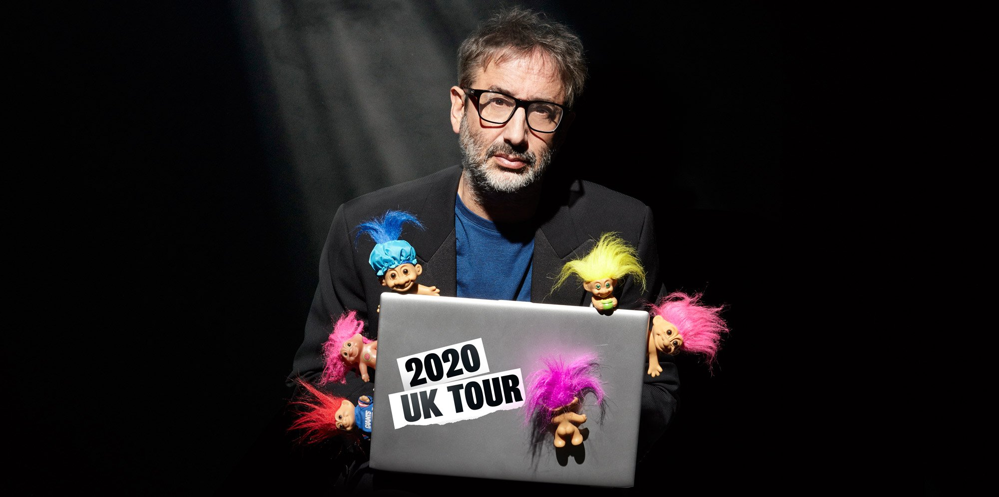 David Baddiel sits on a laptop labelled 2020 Tour, ornamented with multi-colour-hair troll dolls. He sits in the dark, a solo spotlight shining on him.