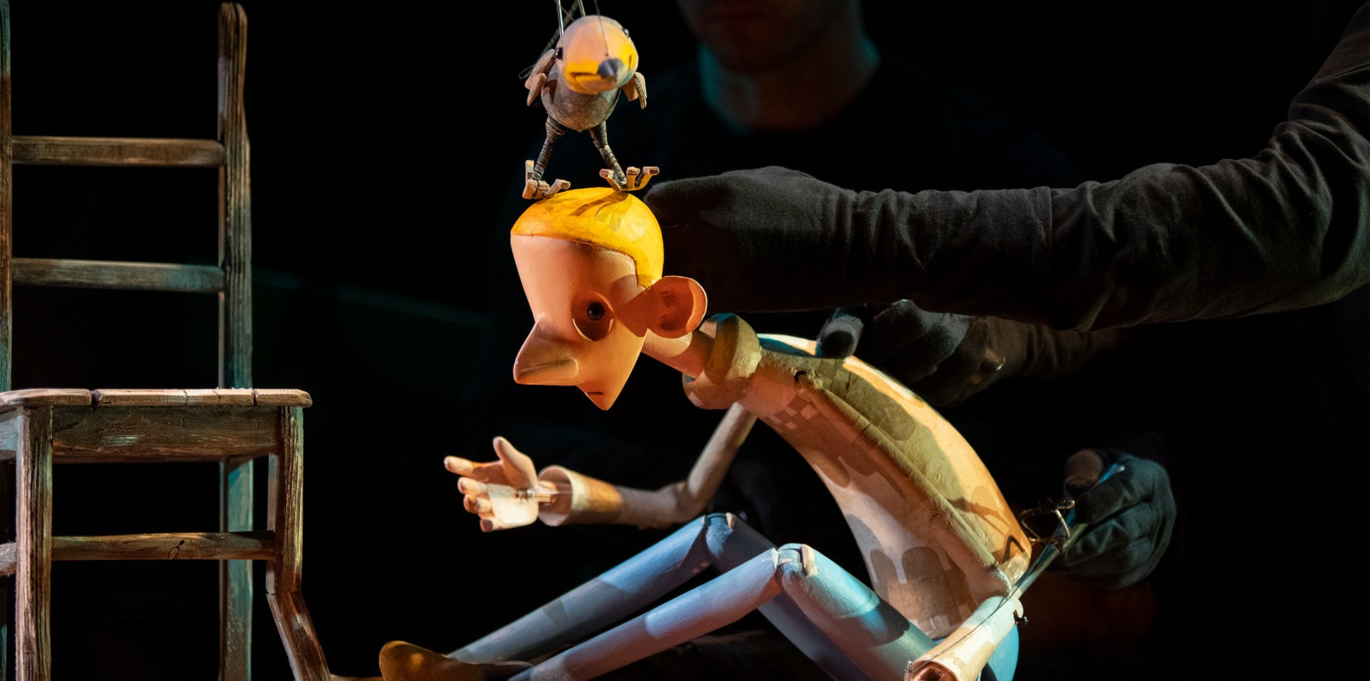 A puppet of a boy with a puppet of a bird on his head