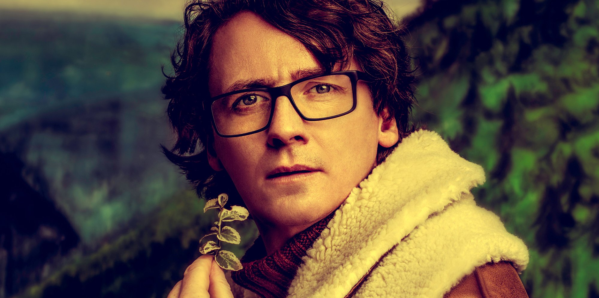 Comedian Ed Byrne looks wistfully, he's holding a small branch with leaves and wearing a woollen jacket