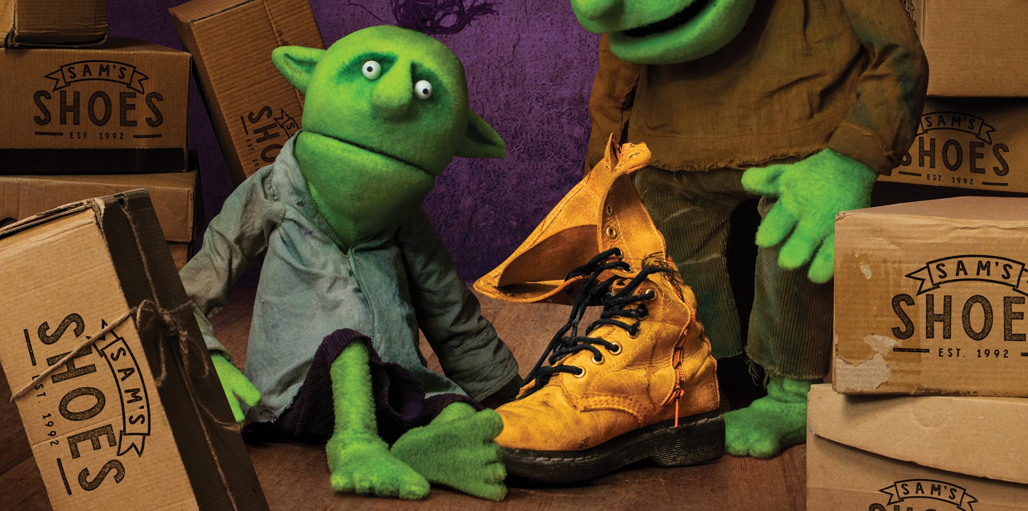 Two puppets of elves are sat and stood with a yellow boot. They are surrounded by boxes that says