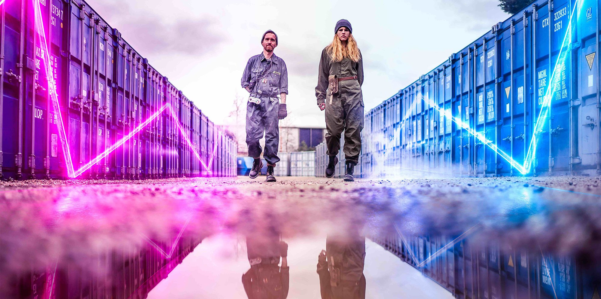 Two performers dressed in boiler suits are in an industrial space with blue and pink neon lights, they are reflected in a puddle of water
