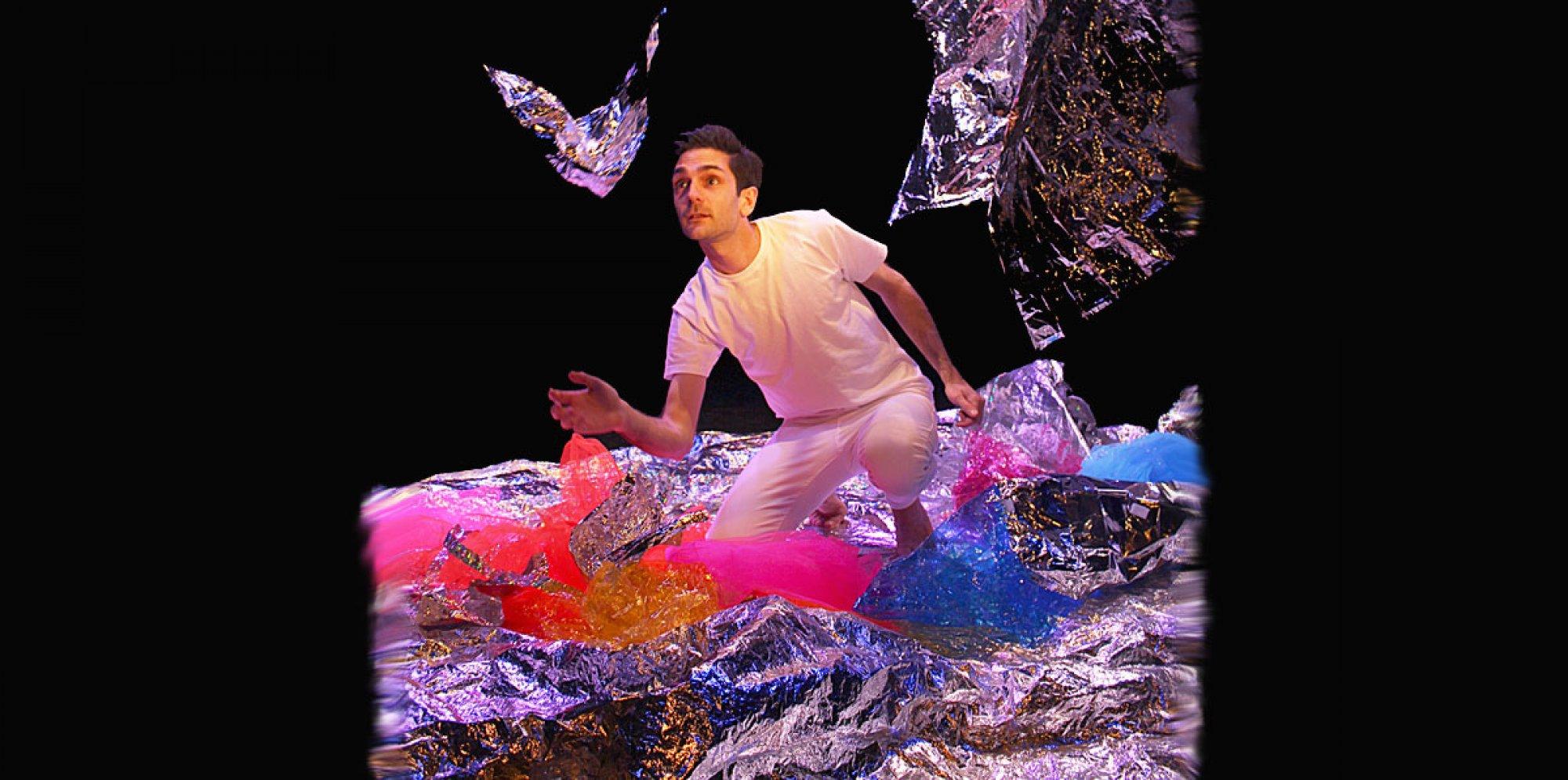 Glisten - The performer kneels amongst glistening foil. A piece of foil flies bird like through the air