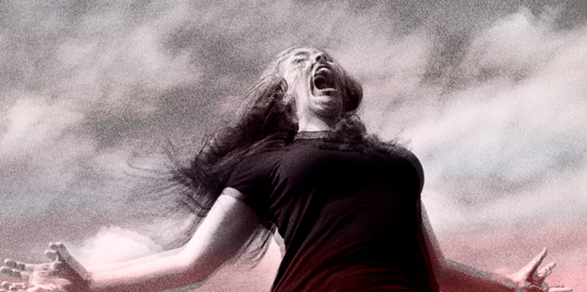 A black and white image of a young woman pictured from the waist up, she is pictured outside and is shouting with her arms outstretched. The image is grainy and has the effect of a badly developed photo.