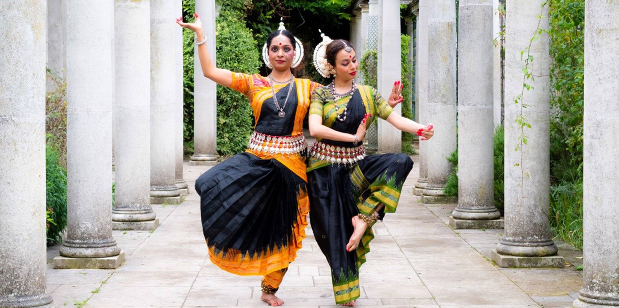 Two dancers strike different poses, they're wearig traditional Indian dance dress
