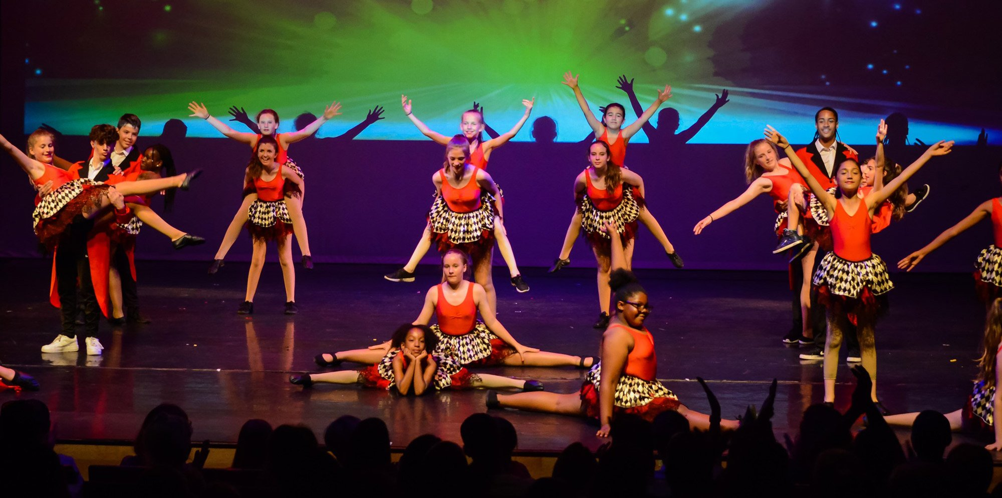 Girls dancing on stage, some of them piggy-back-riding others, others doing the splits