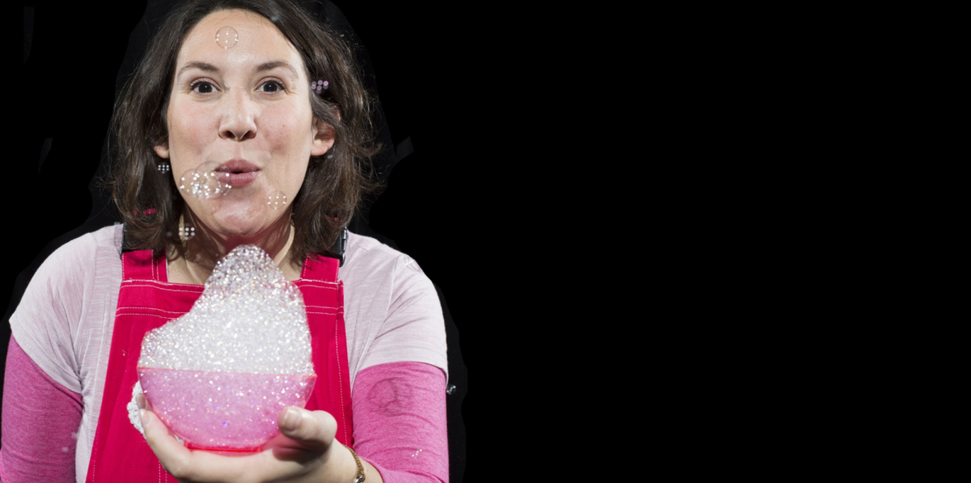 Inside: a person is to the left wearing pink with short brown hair, holding a bowl with bubbles in. They are blowing it