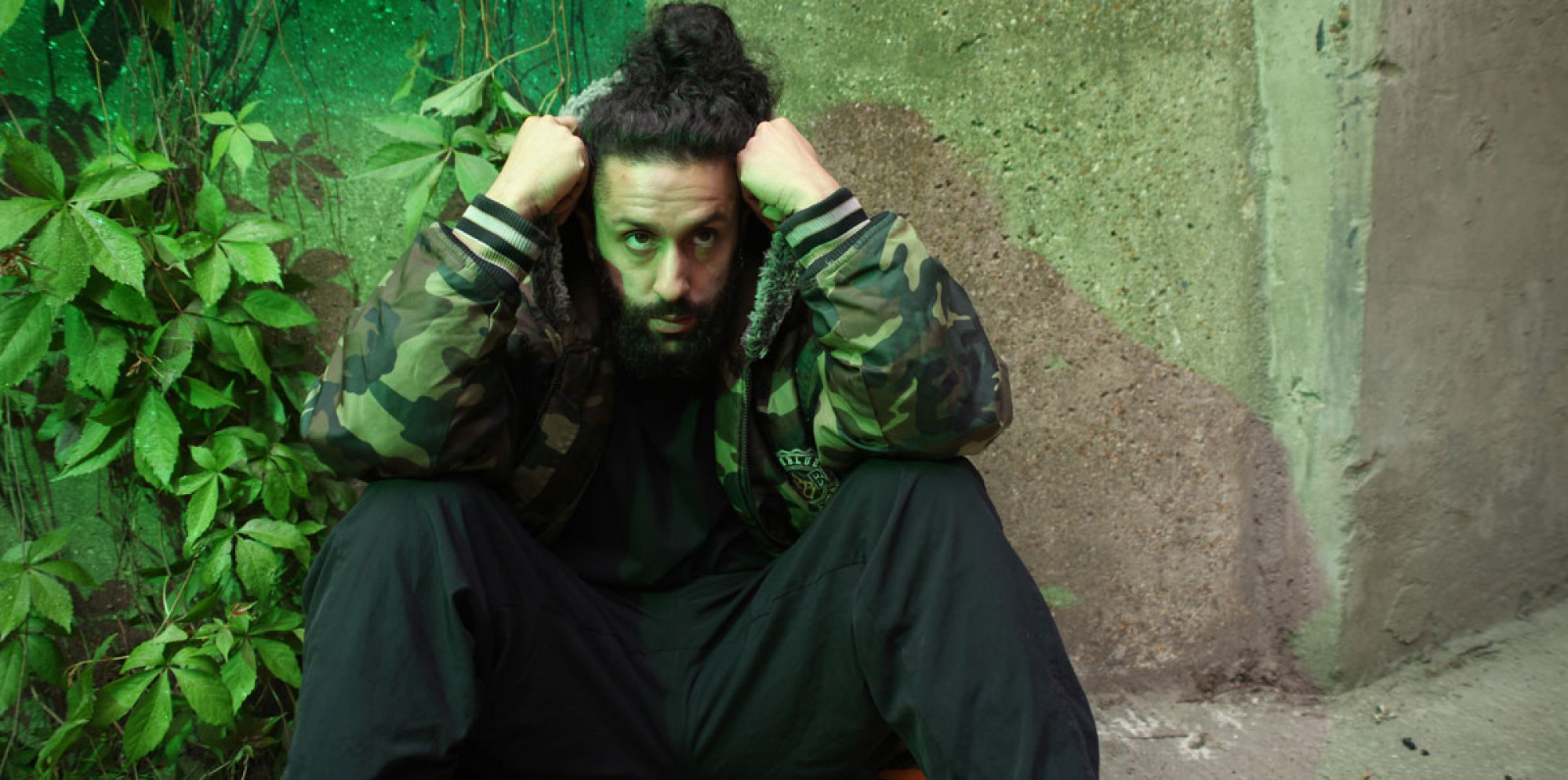 A photo of a man sitting on the ground wearing a green bomber jacket, head in hands, leaning on a vine-covered concrete wall.