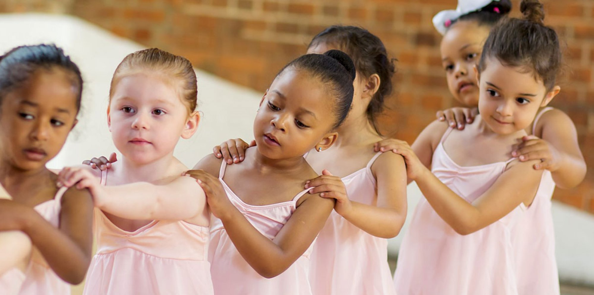 Little London Ballet: six little girls with their hair tied back in soft pink ballet dresses form a line, their arms resting on the shoulder of the girl in front of them. They curiously watch over each others shoulders.