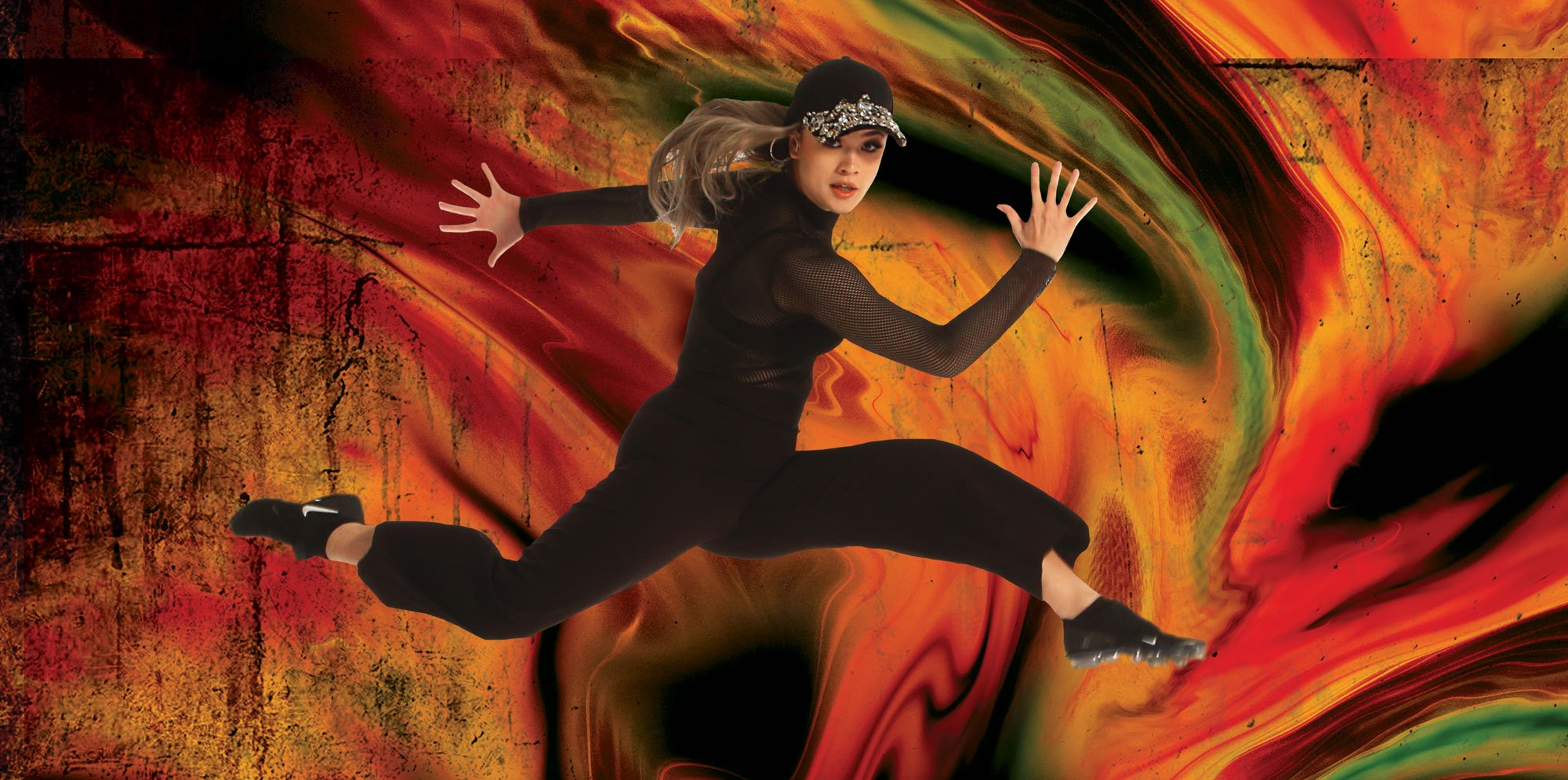 a woman in black clothes and a sparkling baseball hat lunge-jumps in front of a swirling red-yellow background