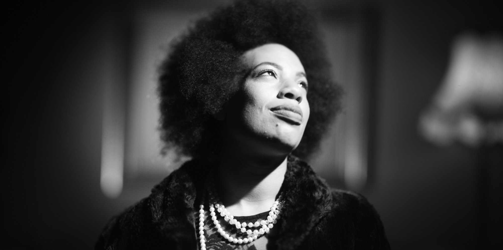 A black woman with natural hair is in a black and white photo. She is looking up and to the side and looks peaceful.