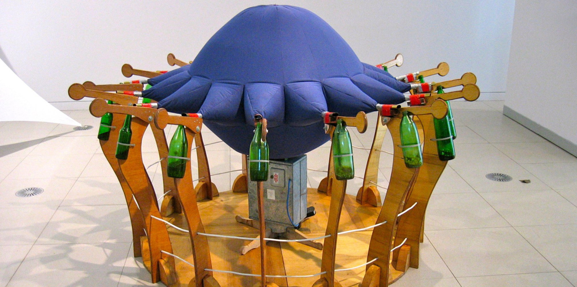 an installation in a wide gallery space. Sat on a wooden pedestal, an inflated blue sphere is attached to a ring of green bottles.