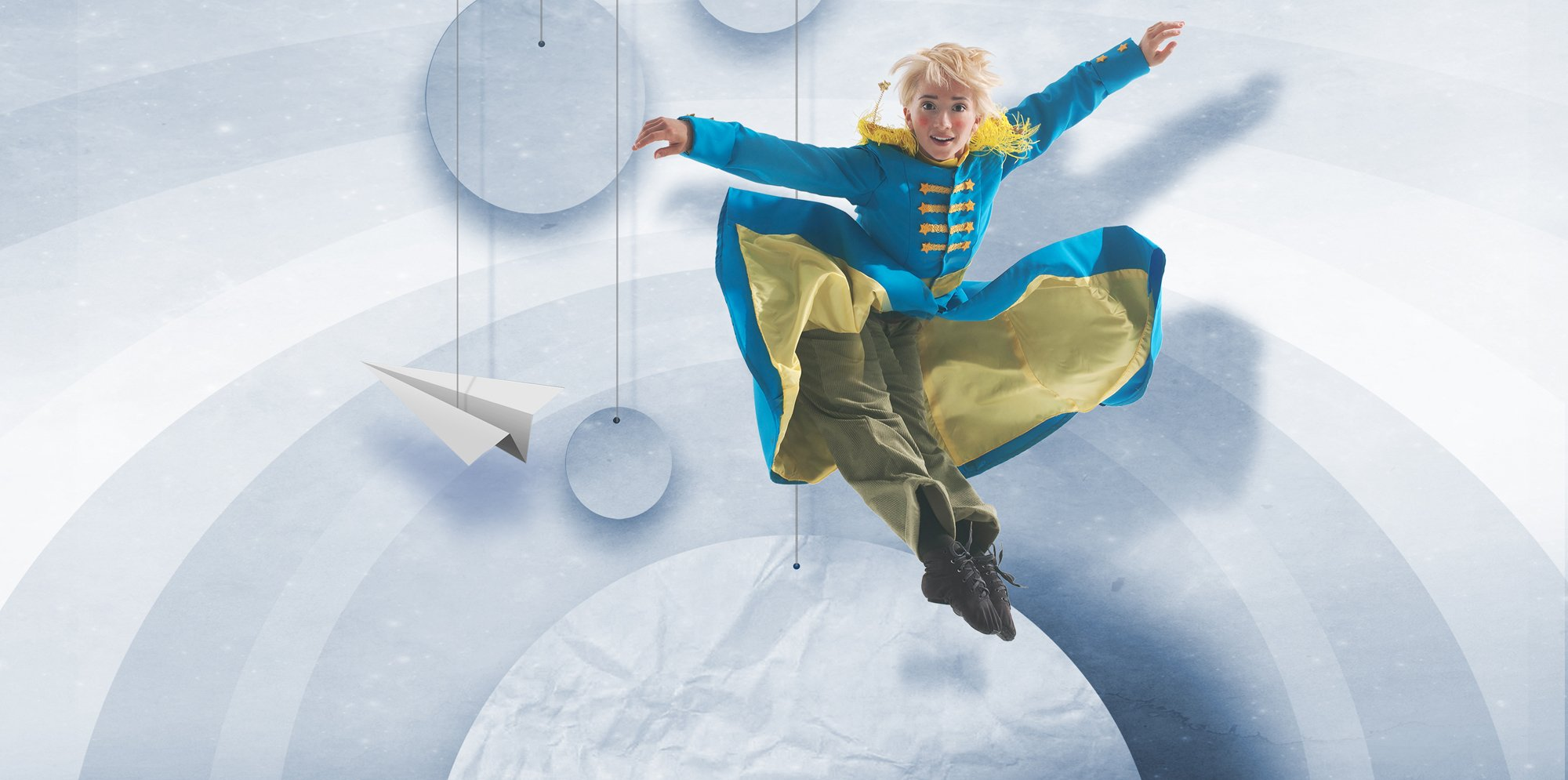 A blonde prince in a blue coat is jumping high in front of a scene of silver planets.