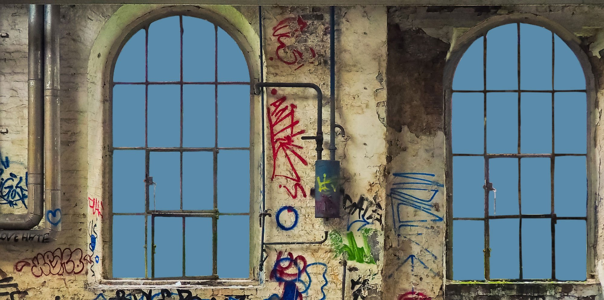 The Local: Two arched windows showing blue sky among graffiti-covered walls