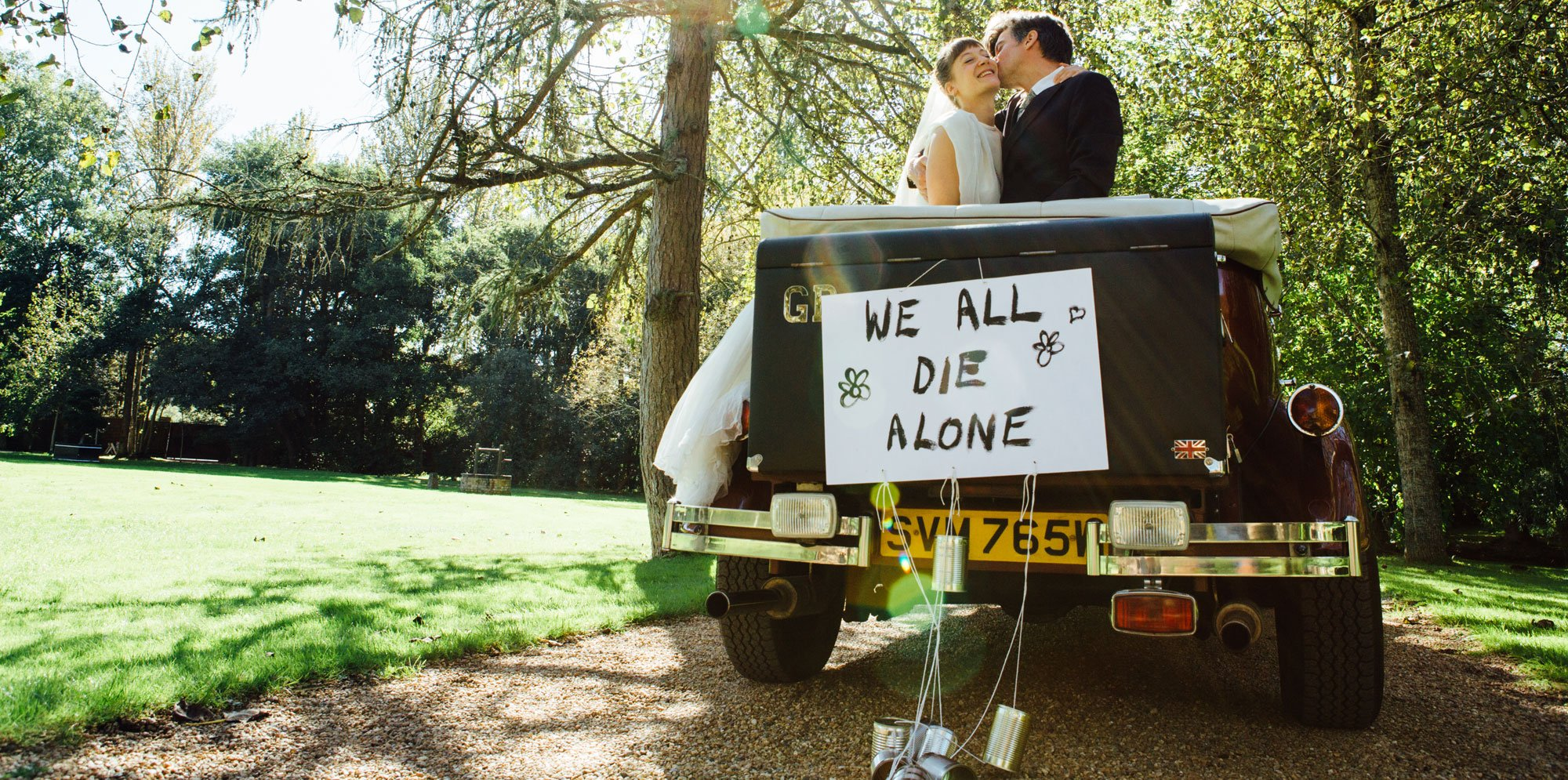 Lost Dog: a wedding couple kissing in an open-roof car, having a