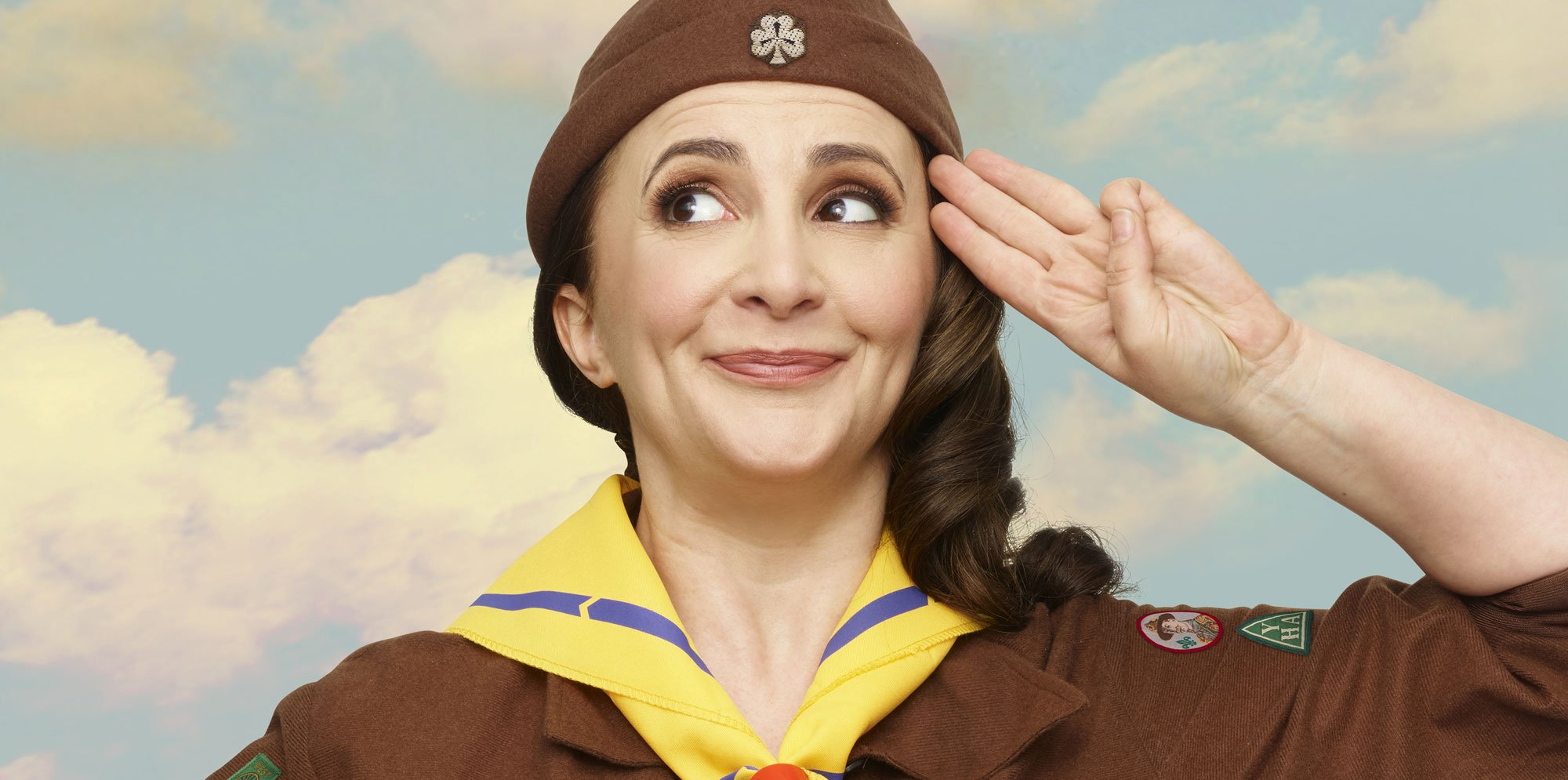 Lucy Porter wearing a brown scout's uniform with a hat and yellow neck cloth. She salutes with a mischievous face.