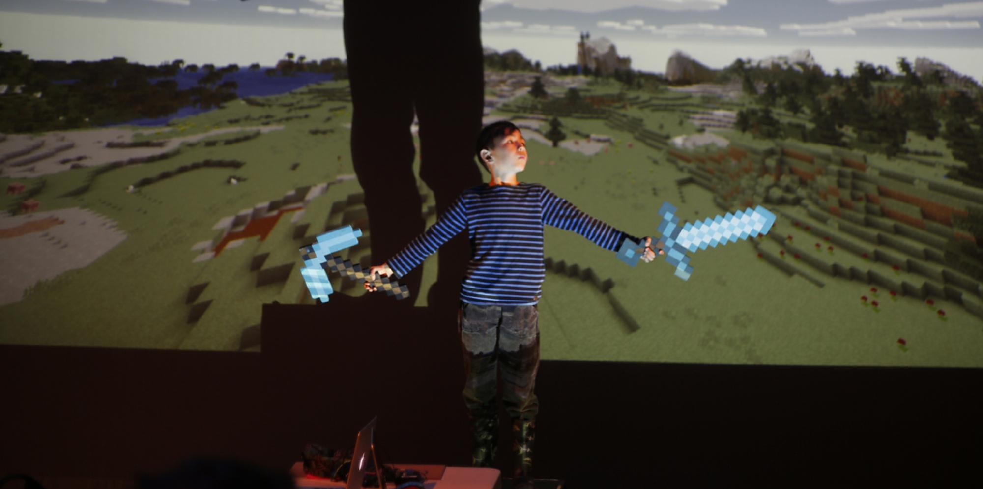 a boy holding up minecraft swords