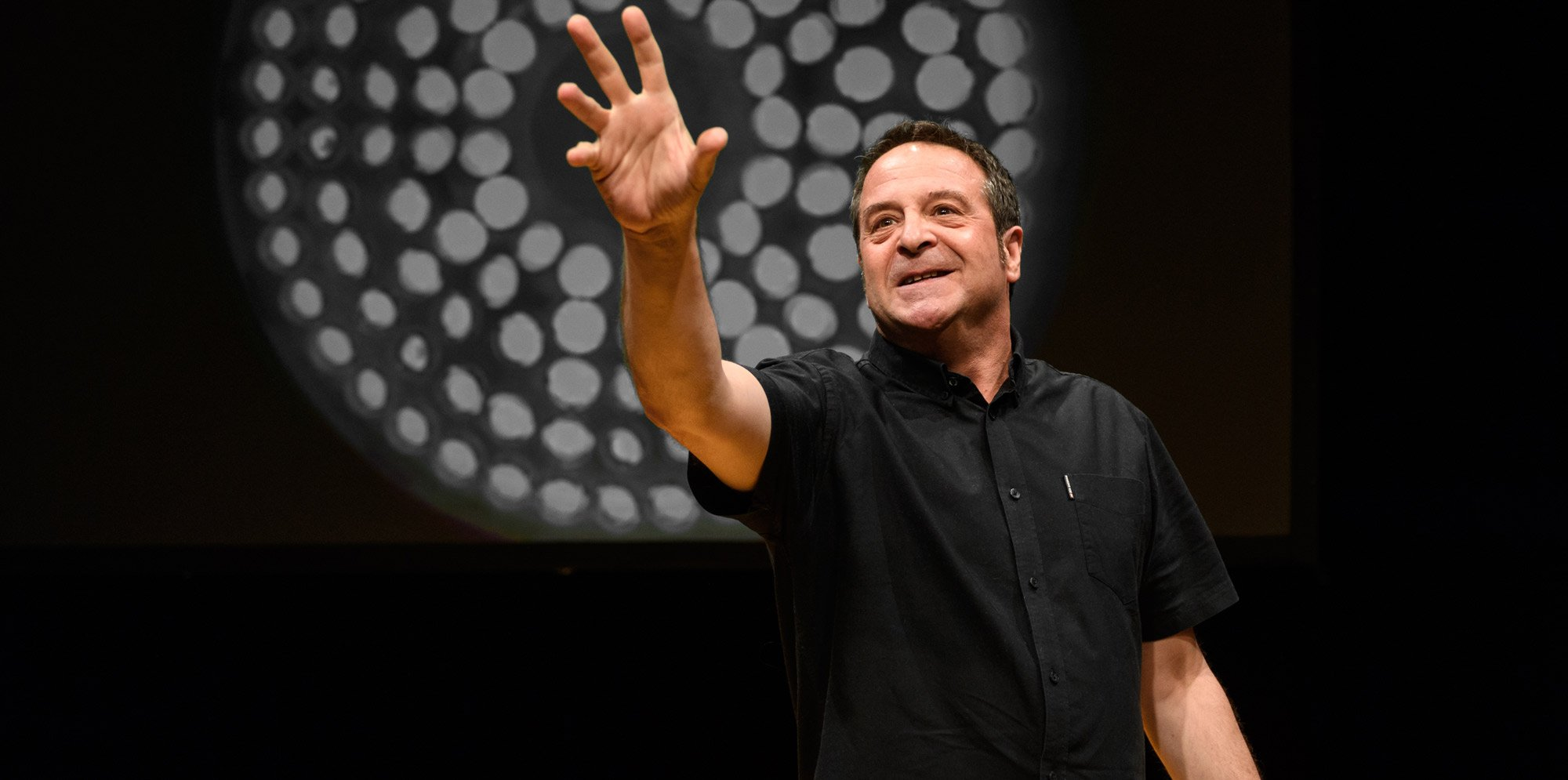 Mark Thomas on a stage, smiling and pointing with his right hand.