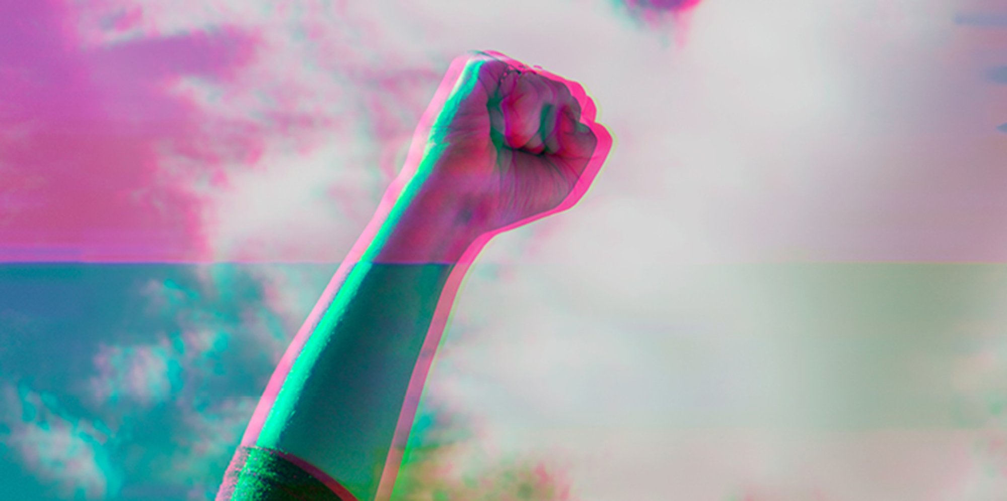 An image of a persons fist held high against a backdrop of the sky. The colours of the image are strange, as if it's a badly developed photograph.