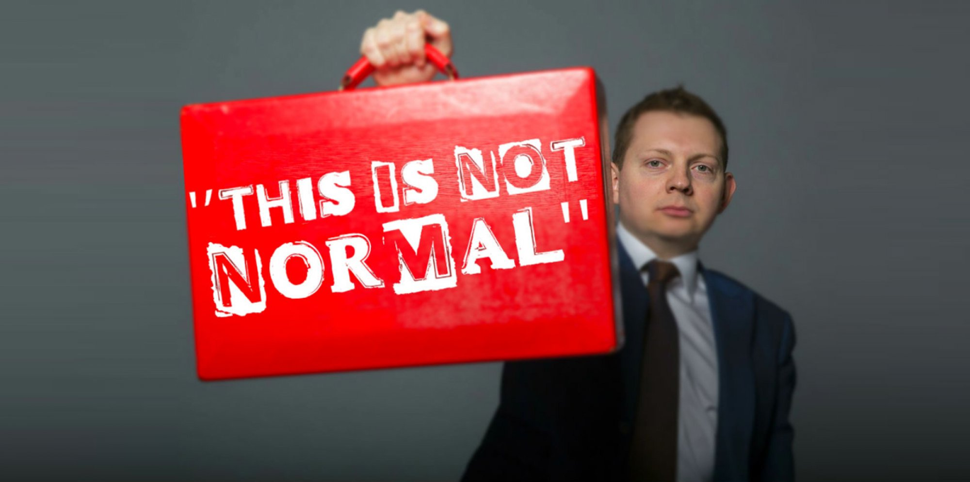 Matt Chorley: A man in a suit holds up a red briefcase that's labelled