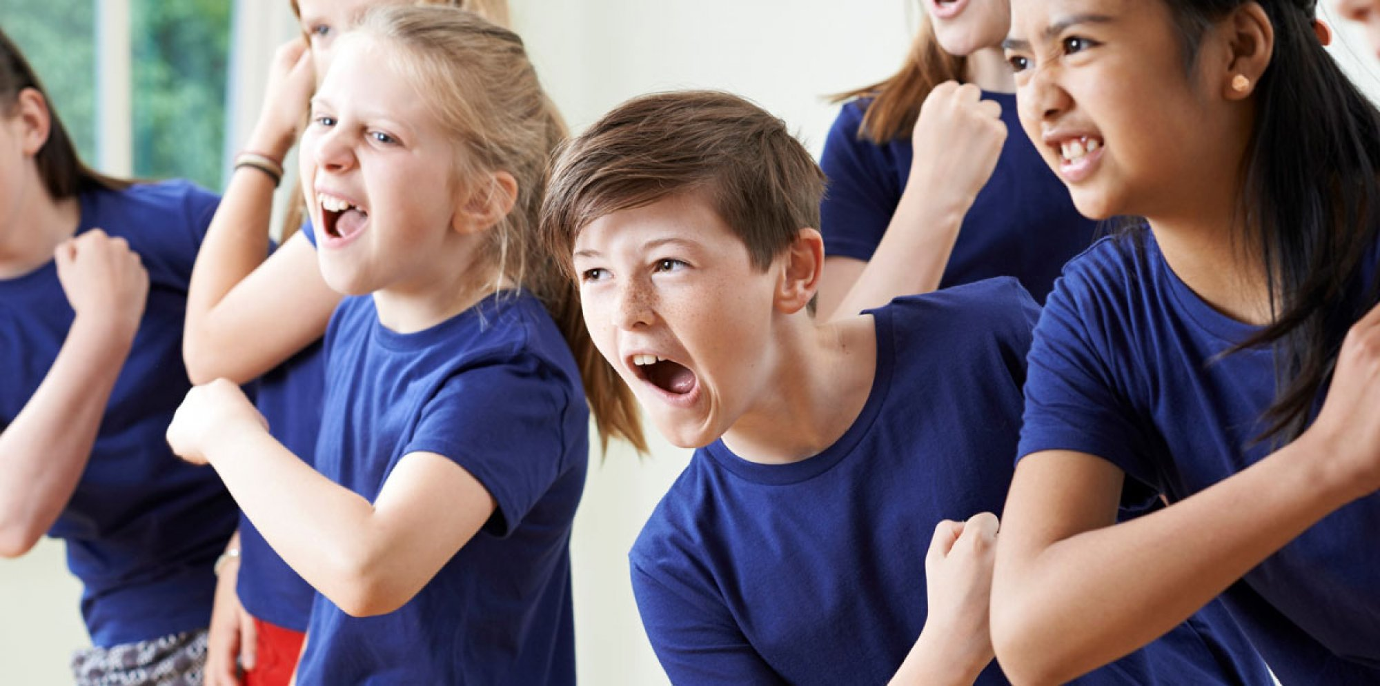 Two kids dressed in blue chanting enthusiastically