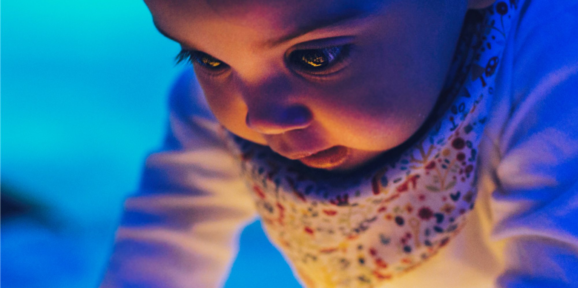 a baby's astonished face lit up by a yellow light source