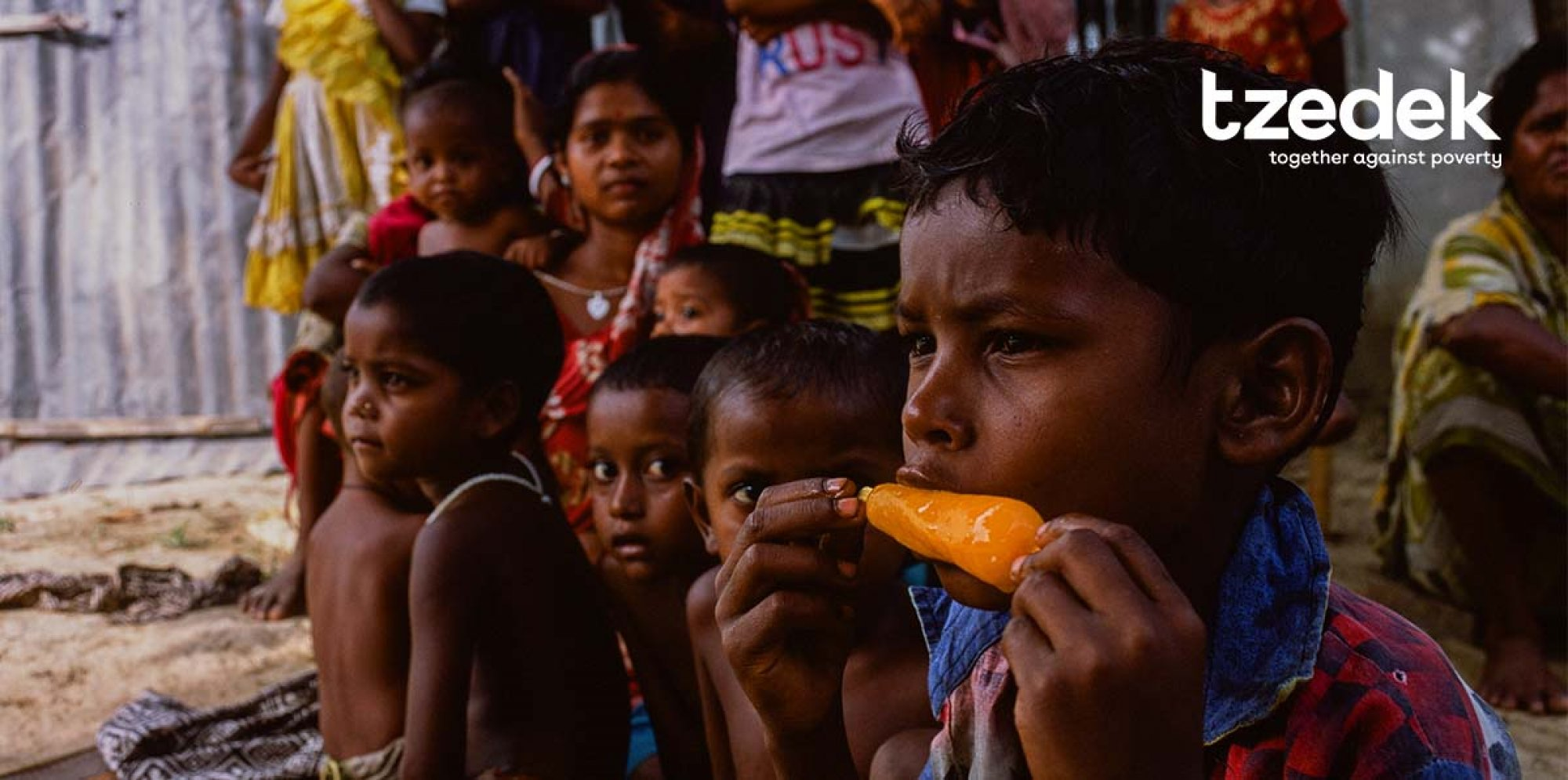 a group of brown children sit in a row. The one closest to the viewer is eating an orange ice lolly, looking pensive. The two next to him watch him, the fourth is looking straight-ahead.