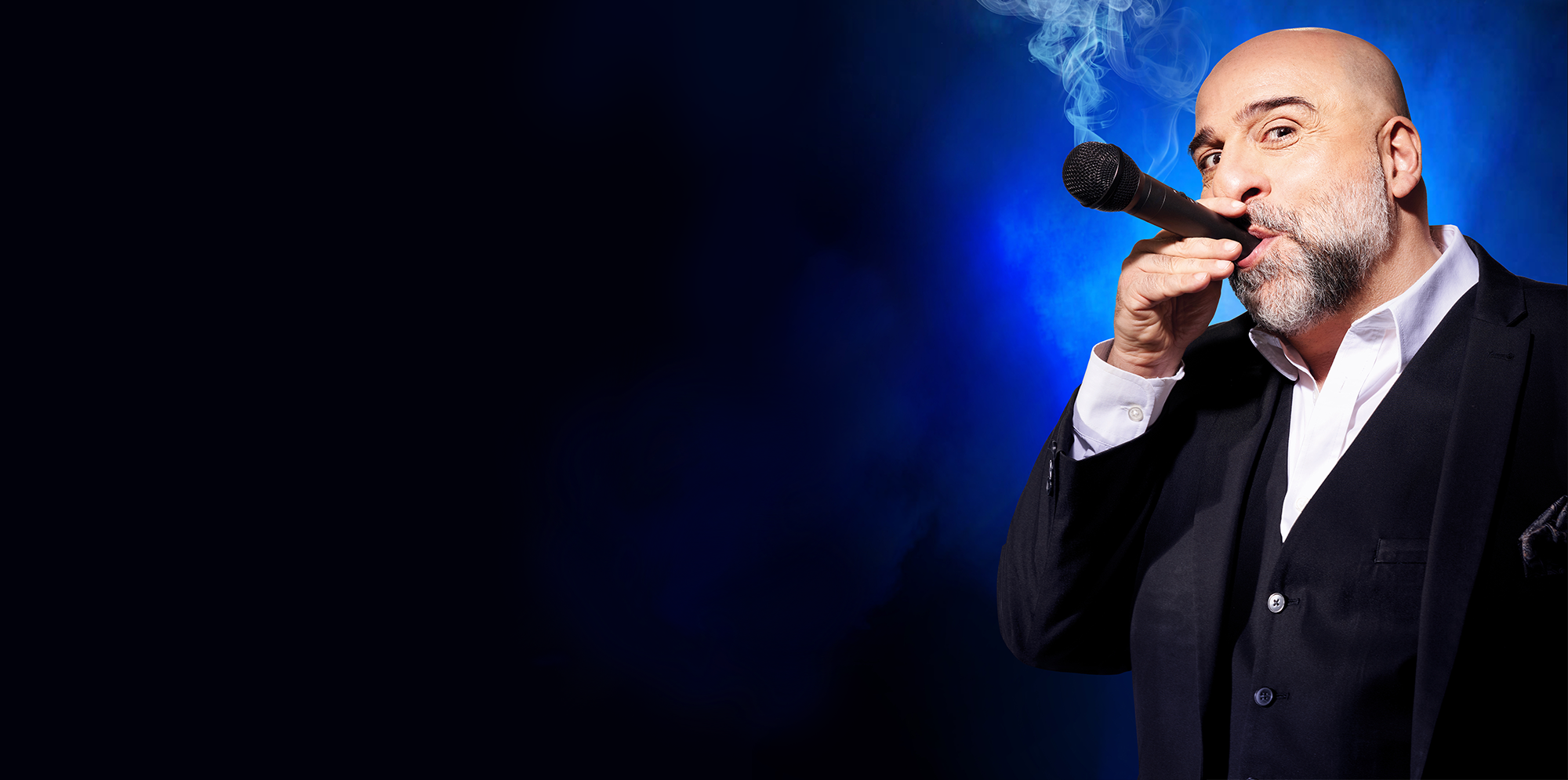 Omid Djalili, wearing a dark suit is looking at the camera and using a microphone as if it's a cigar