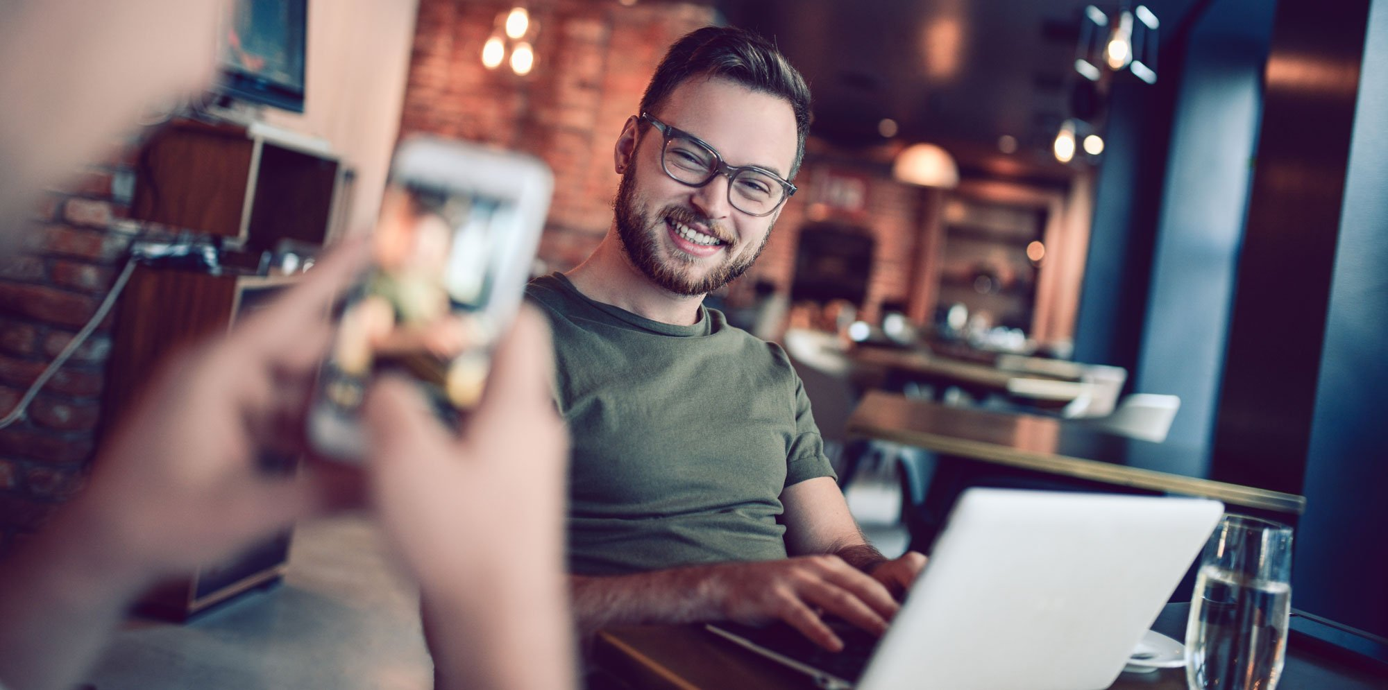 in a cafe, a man takes a picture on his phone of another man on his laptop