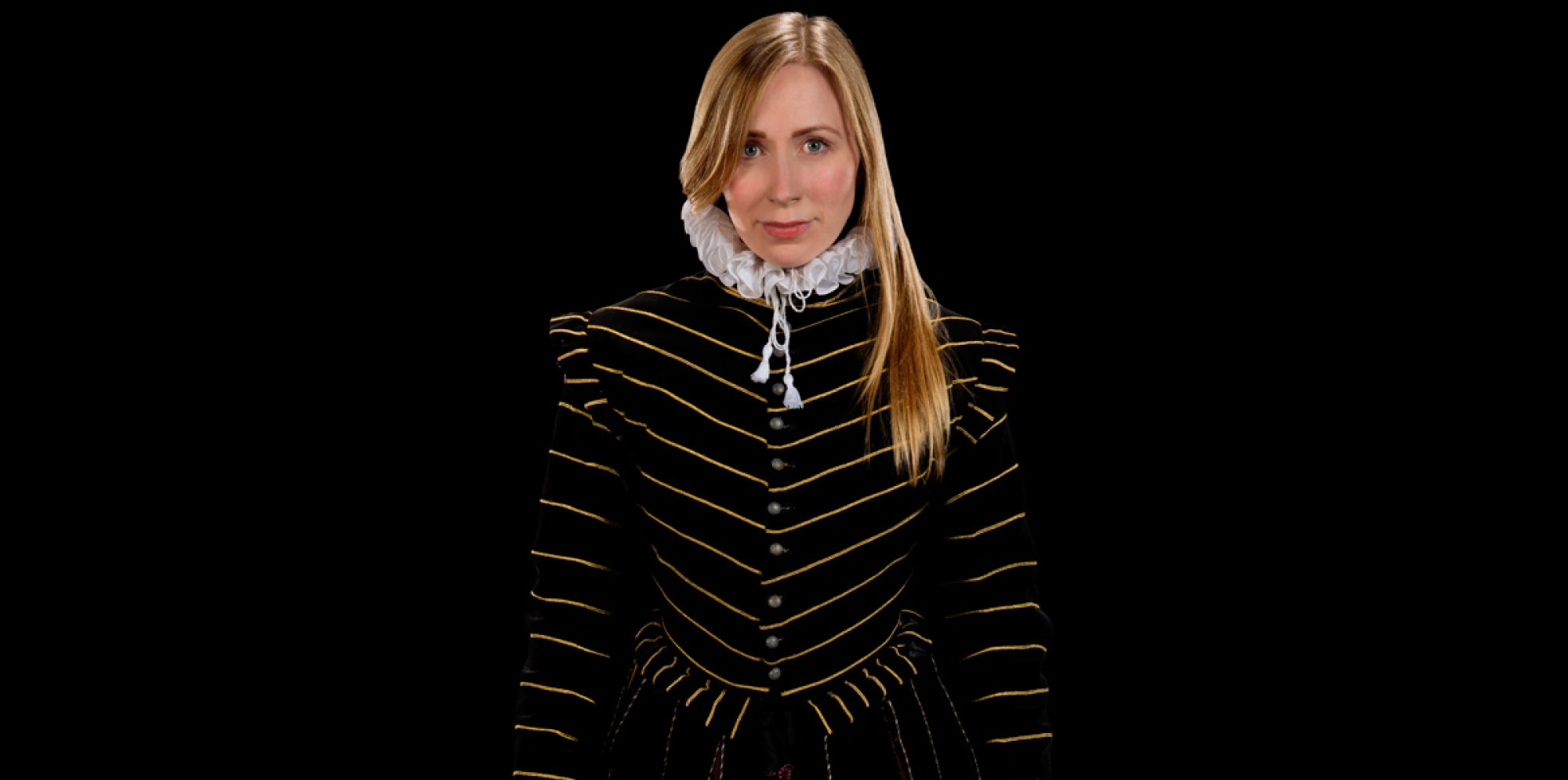 Rebecca Vaughan looking confident at the viewer, dressed in a black-golden Tudor male jacket