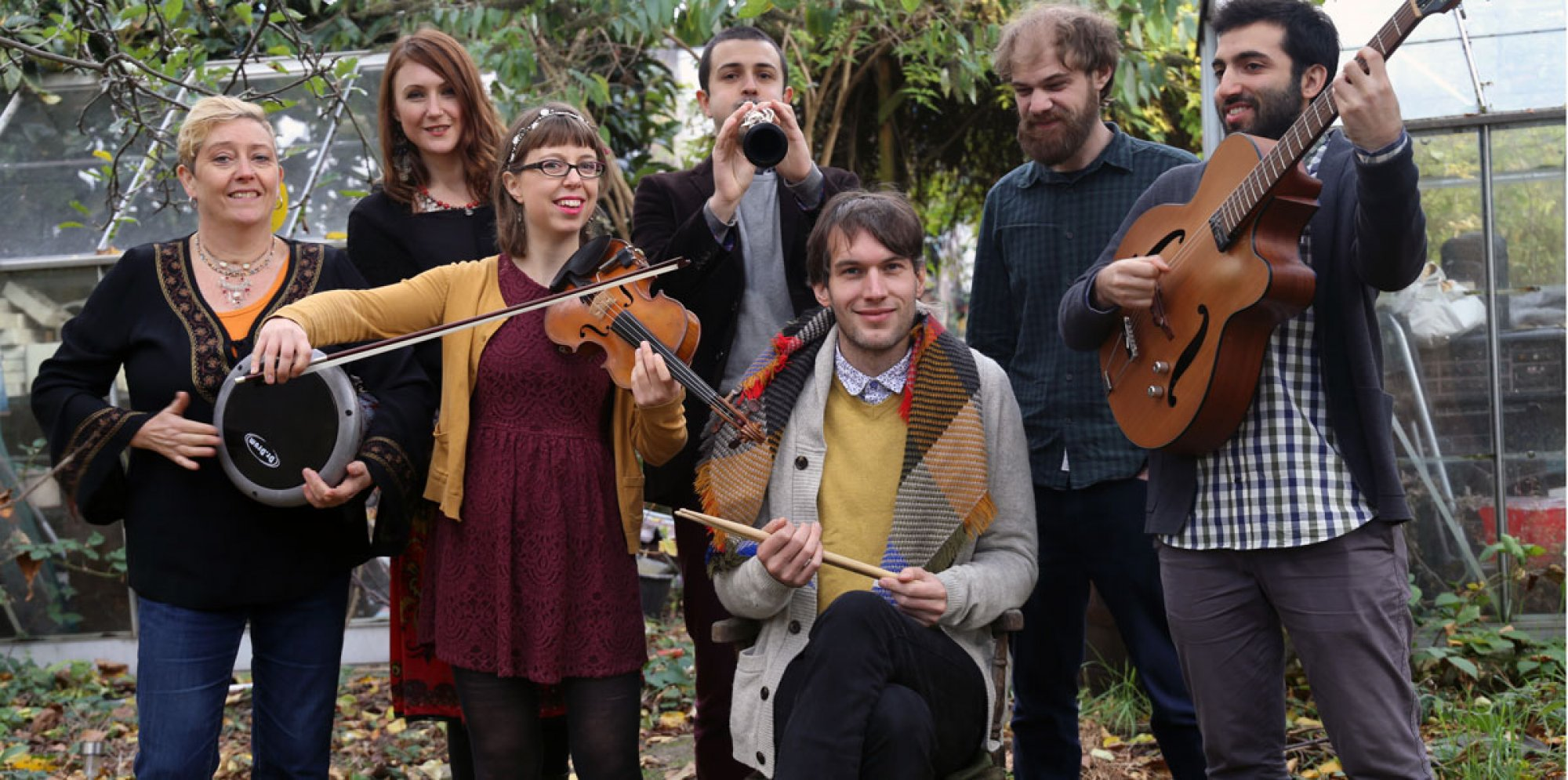 A group photo of musicians holding instruments including violins, guitar, drums and flute.