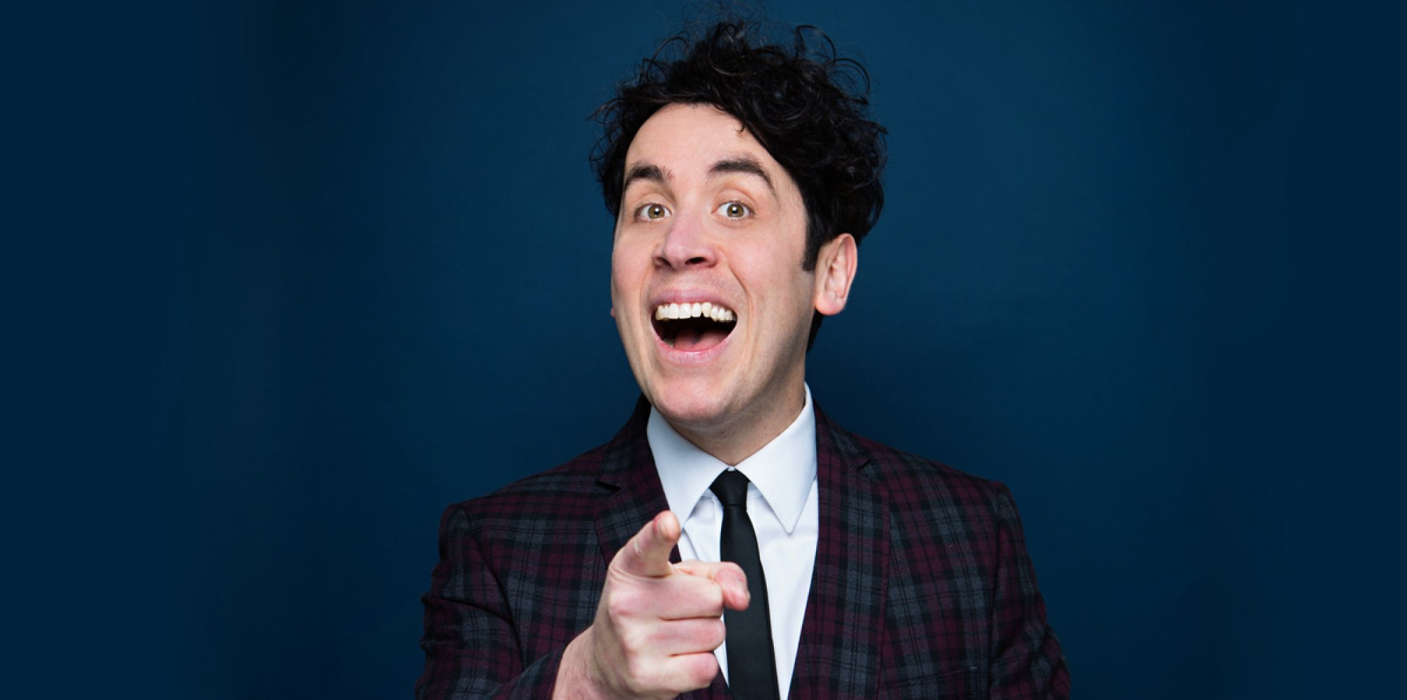 Pete Firman smiling and pointing at the camera in a