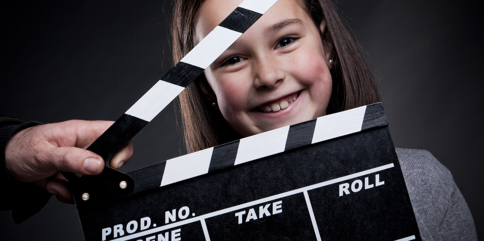 a girl smiling from behind an open clapperboard