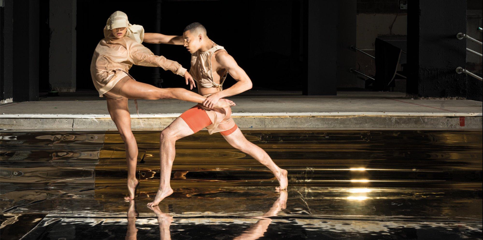 Rambert Dance Rambert2 two young dancers in nude clothing dancing in an empty space