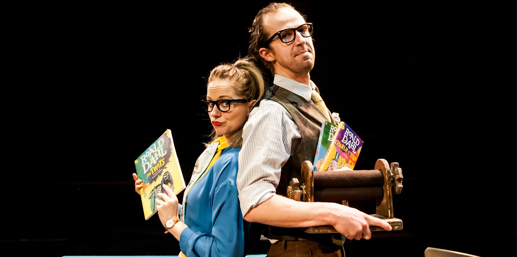 Roald Dahl: A man and a woman stand bacl to back. She holds up a Roald Dahl book, he holds a spindle, more Roald Dahl books pressed against his chest