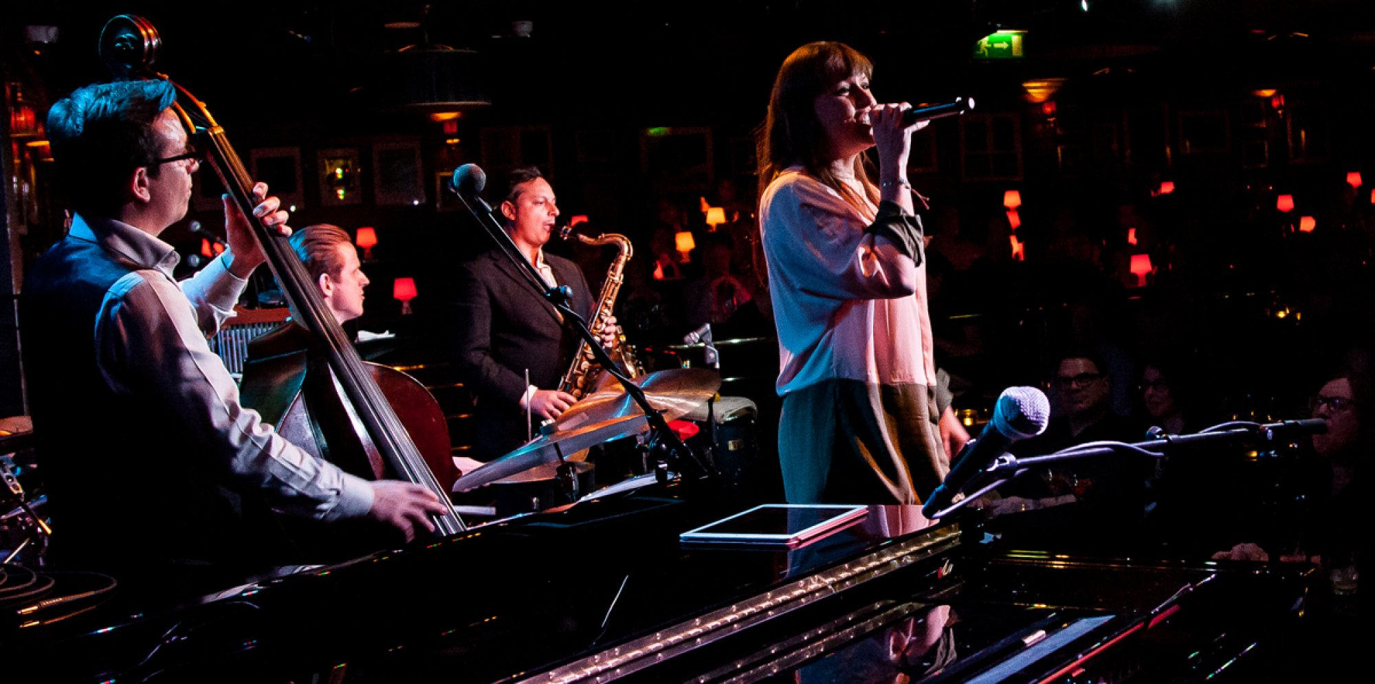 a female performer singing into a mic with a jazz band behind her