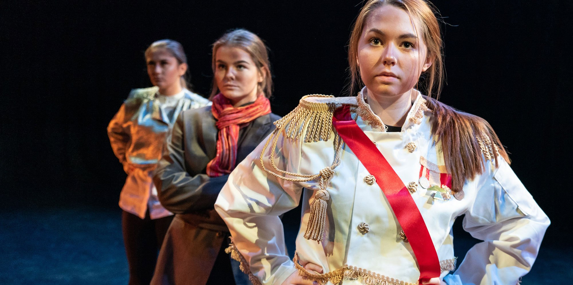 Shakespeare Schools Festival: three girls stand behind each other, staggered to the side. The girl in front is wearing a white royal uniform.