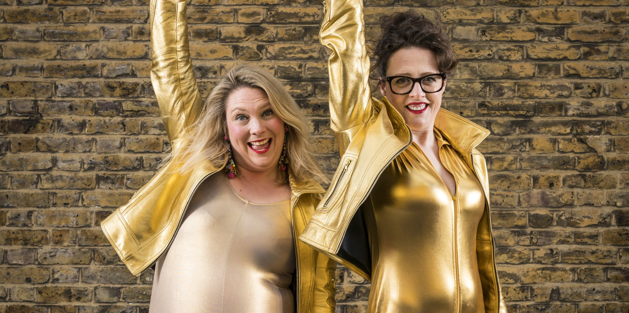 Two women in gold clothing smile at the camera.