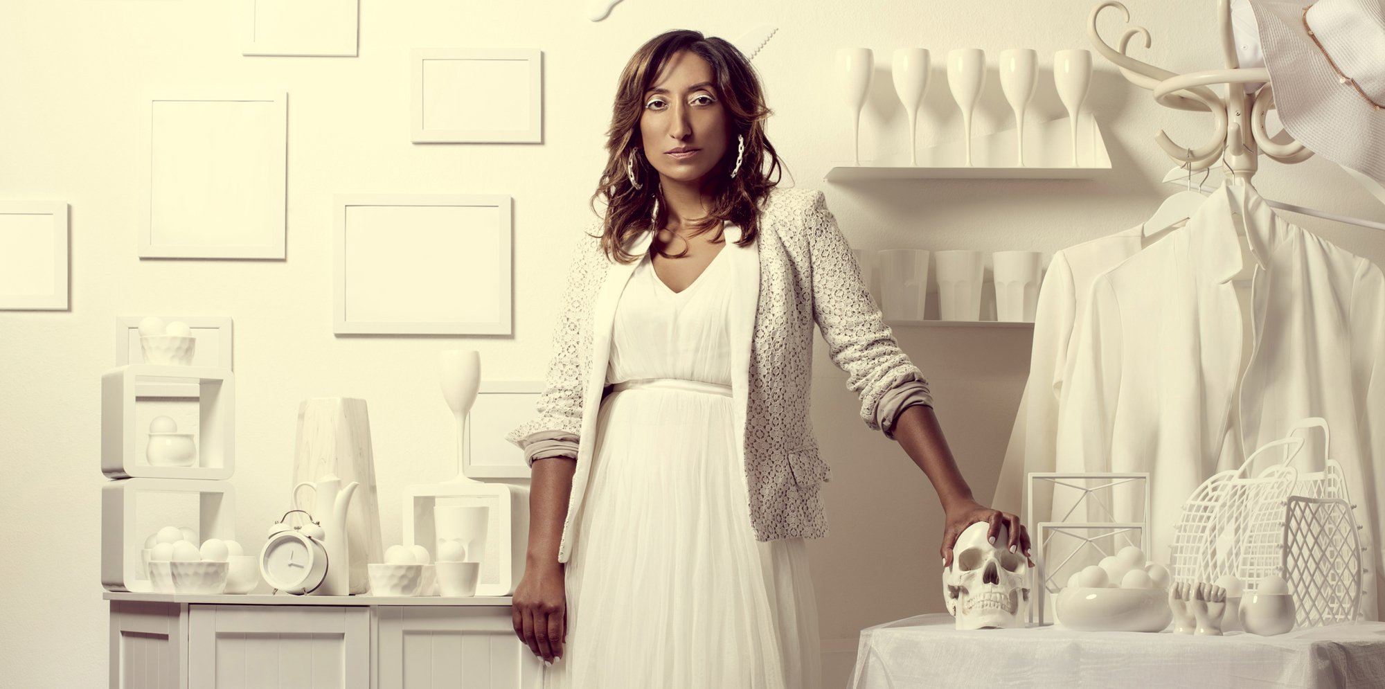 Shazia Mirza, dressed in a white dress and white jacked stands in front of a background made up of white objects. Her hand is resting on a skull.