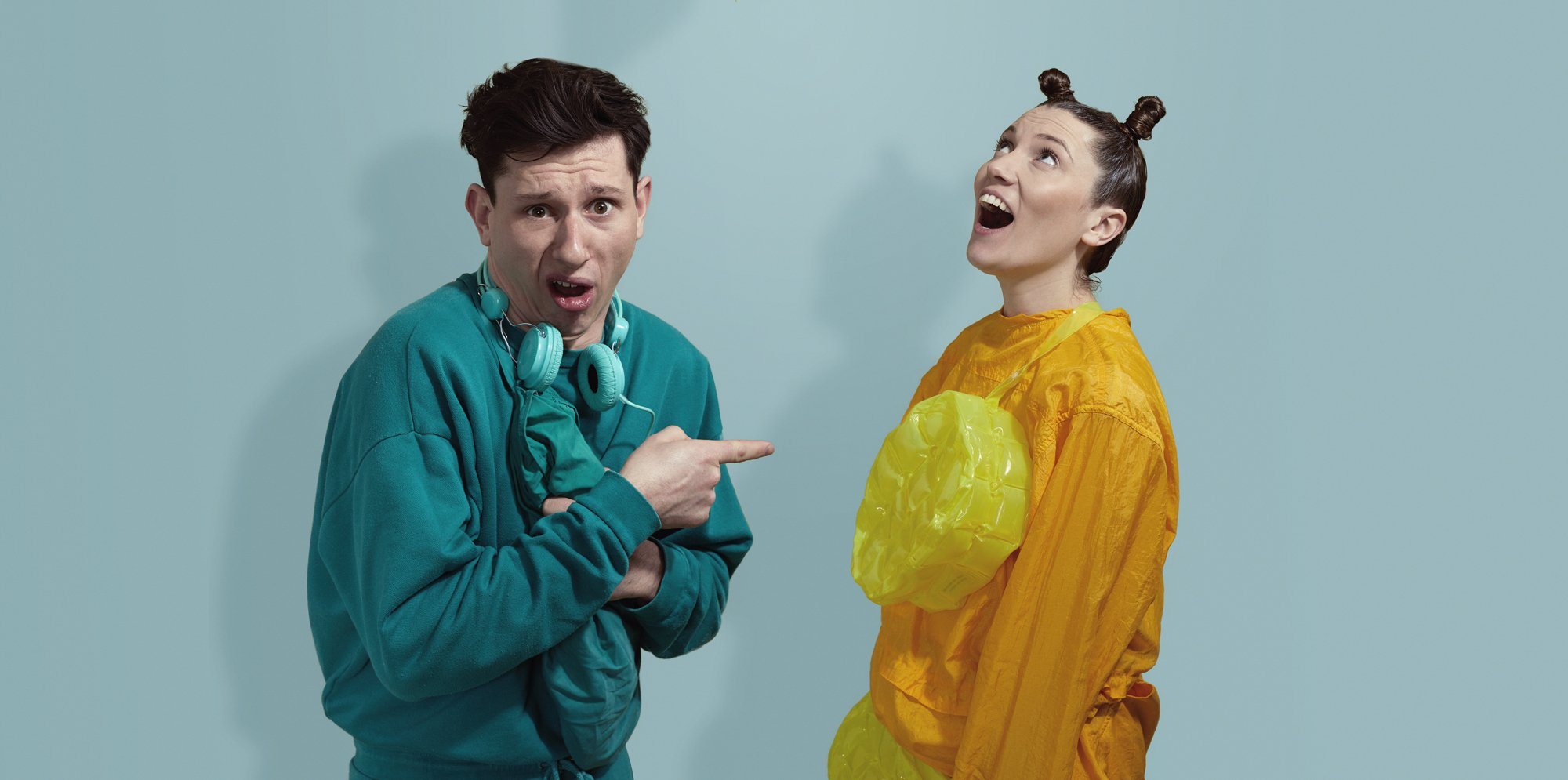 A man in blue as a caterpillar and a woman in orange as a slug look up at a leaf