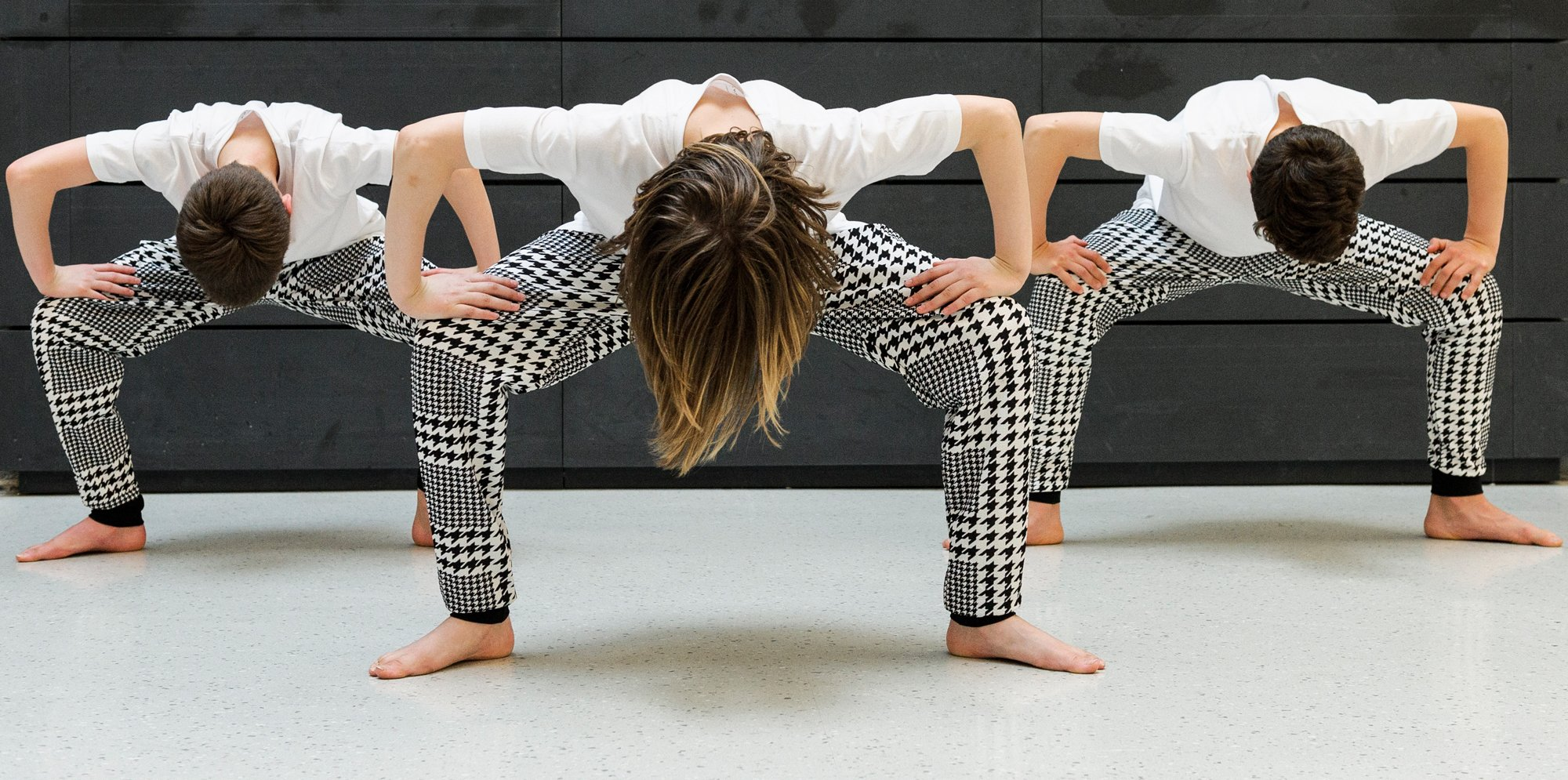 Three people dancing in front of a black wall. They stand with their legs turned out and bent over, so you only see shoulders, the tops of their heads and their legs in black-and-white patterned trousers.