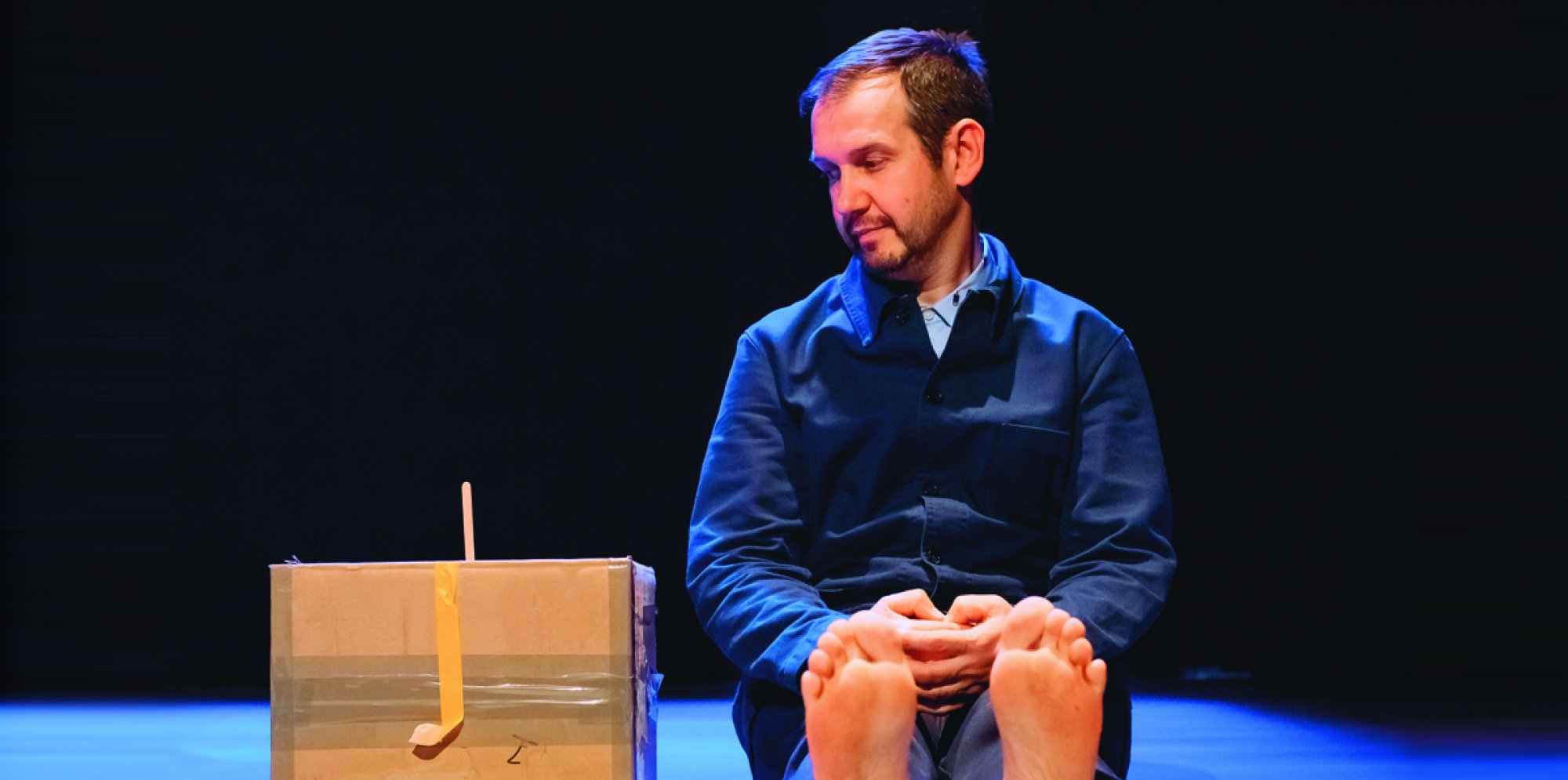 Stick by Me: on a dark stage sits a man looking down at a box