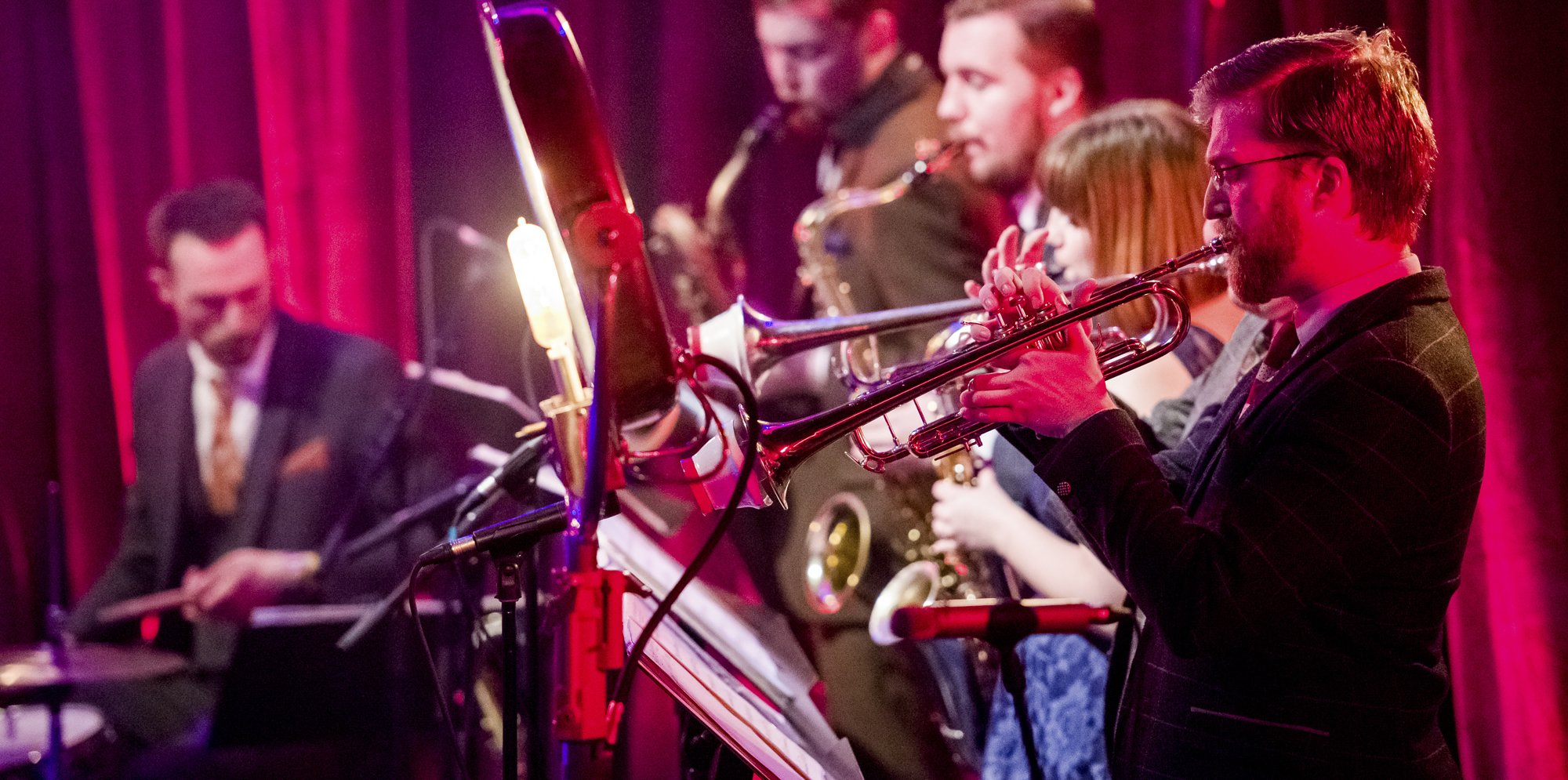Swing That Music: a small big band, with a drummer, three people on saxophones and trumpet and in the foreground a man playing the trombone