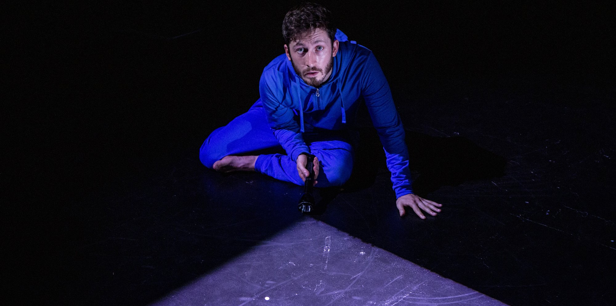 A man is on the ground in a blue onesie, holding a torch. The light from the torch is in front of him.