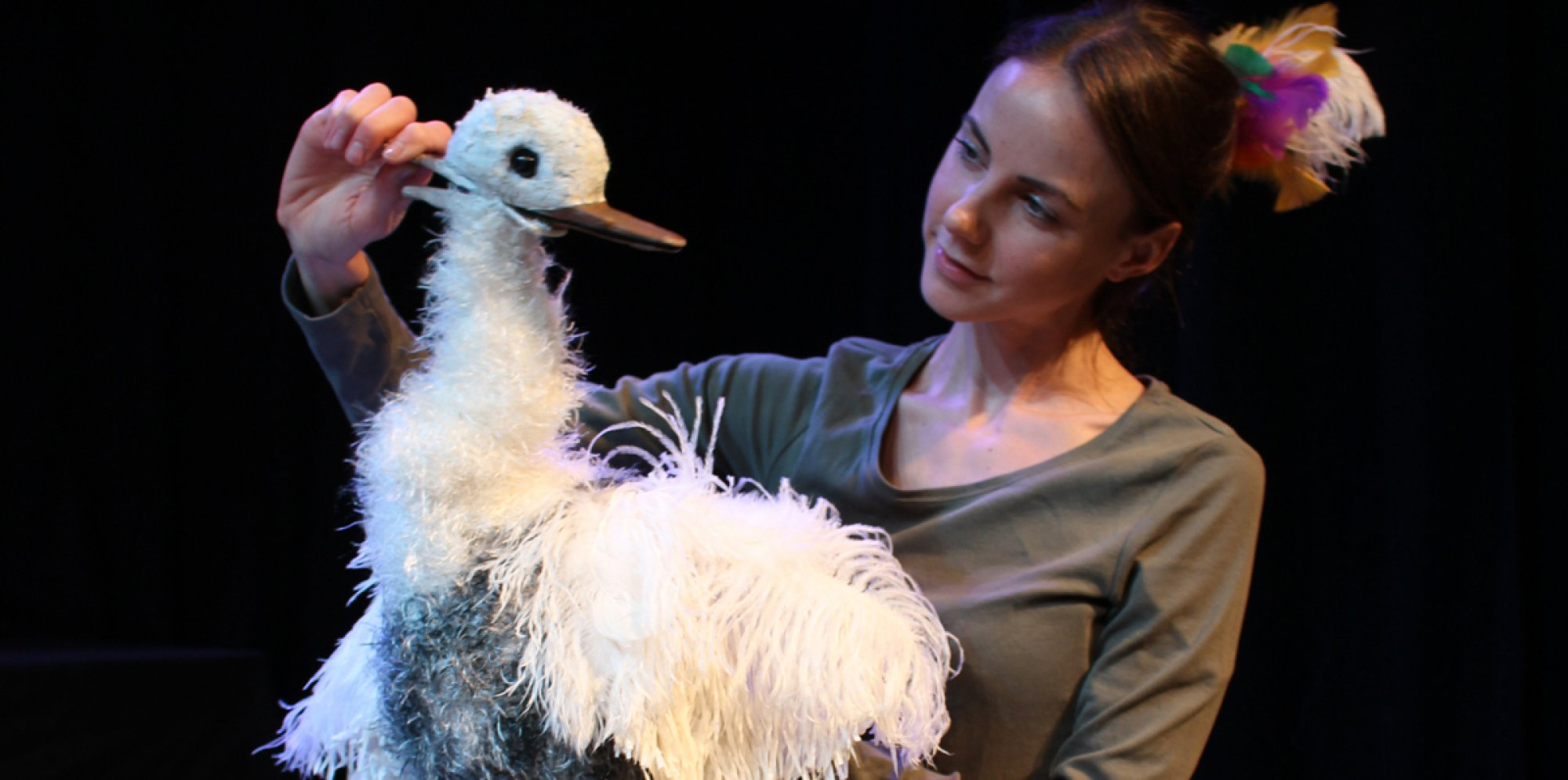a puppeteer holding and looking at a puppet of a fluffy white goose