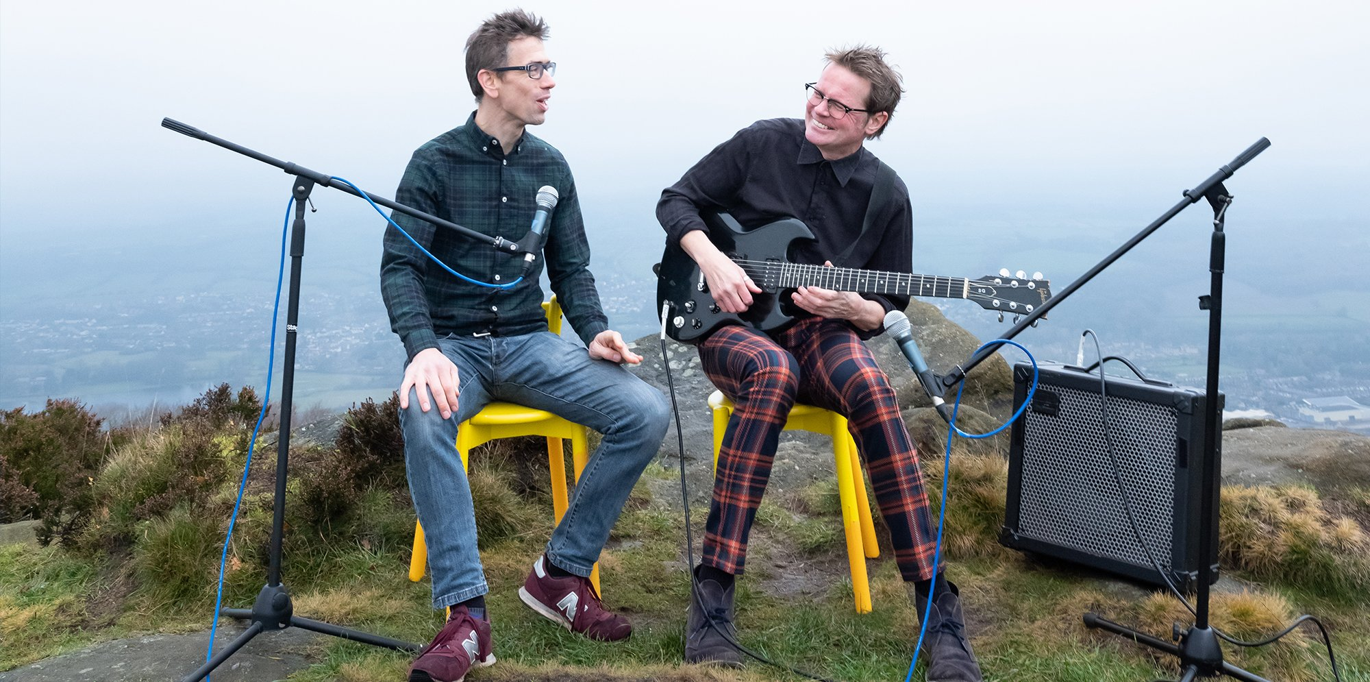 Two musicians are sat on a mountain top with guitars and microphones