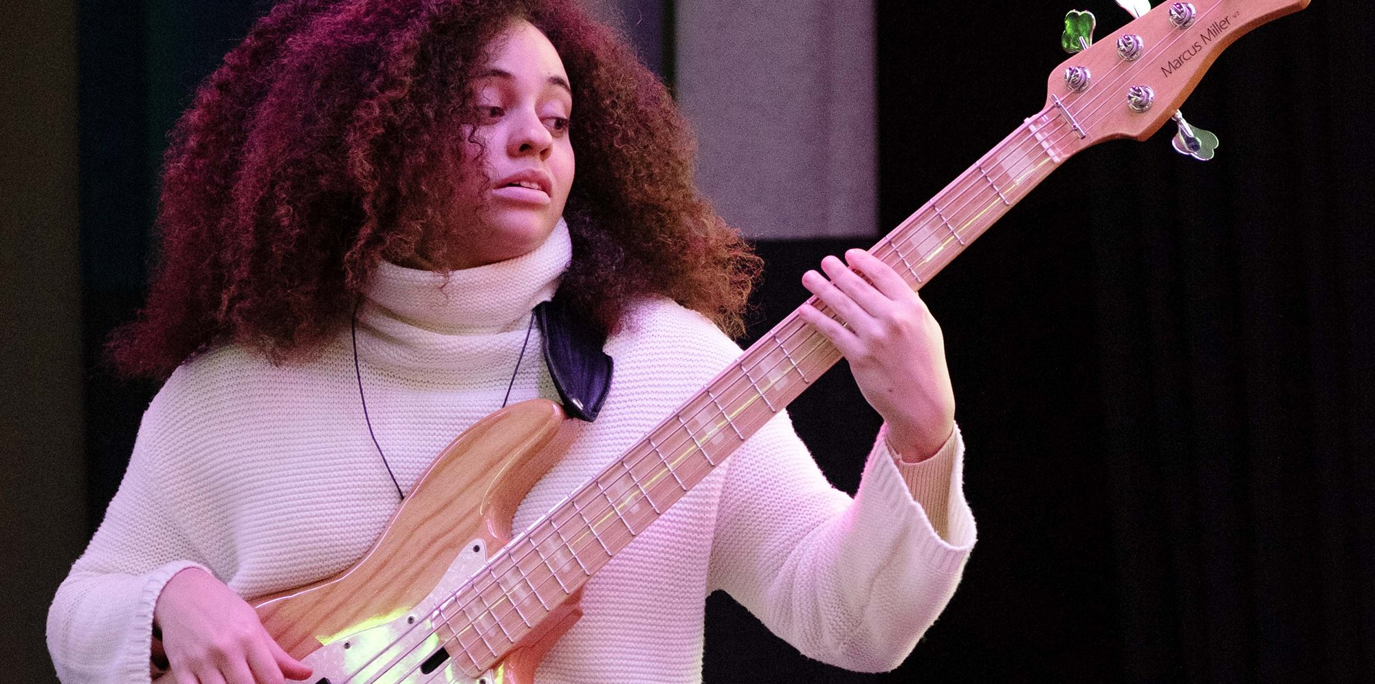 A woman in a beige sweater is playing the bass guitar.